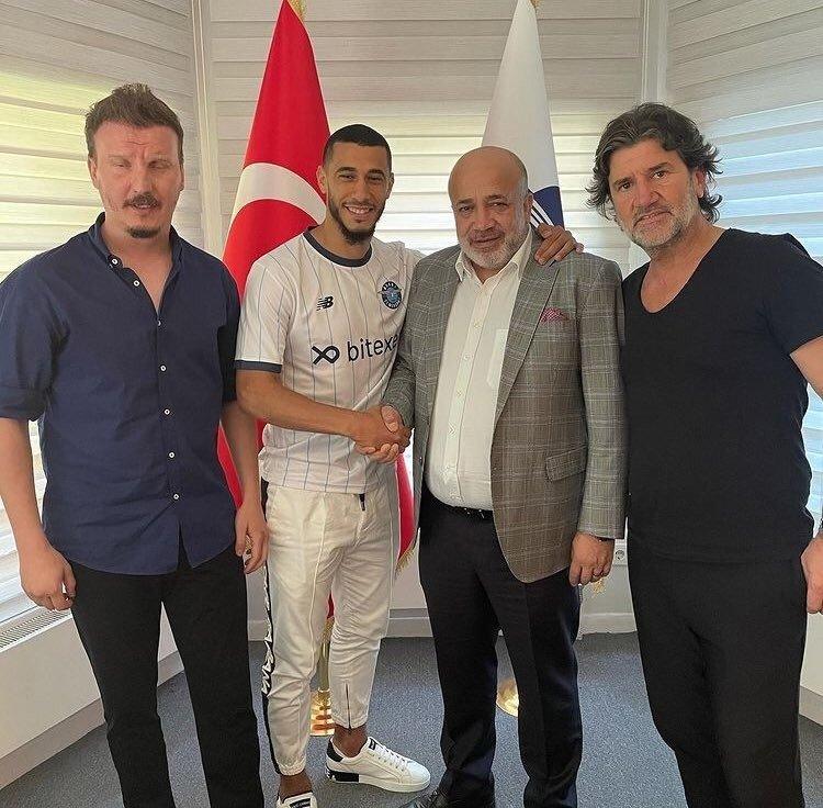 Moroccan midfielder Younes Belhanda (C-L) shakes hands with Adana Demirspor President Murat Sancak (C-R) at the club headquarters in Adana, Turkey, July 1, 2021 (IHA Photo)