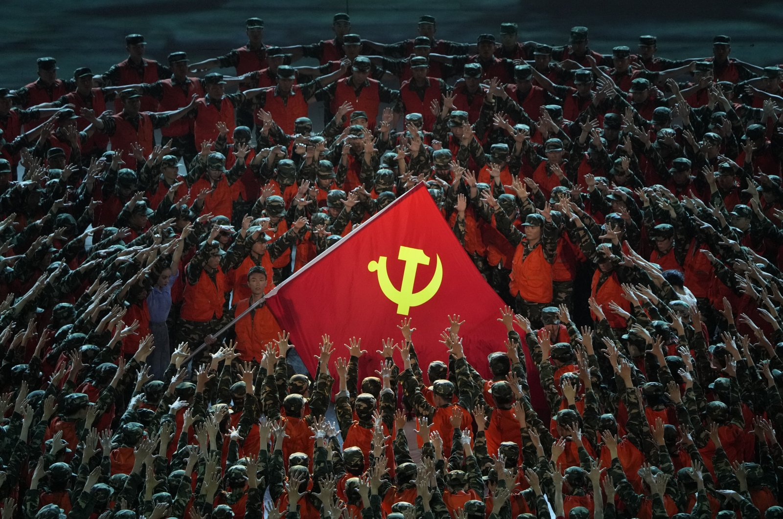 Performers in the role of rescue workers gather around a Communist Party flag during a gala show ahead of the 100th anniversary of the founding of the Chinese Communist Party in Beijing, China, June 28, 2021. (AP Photo)