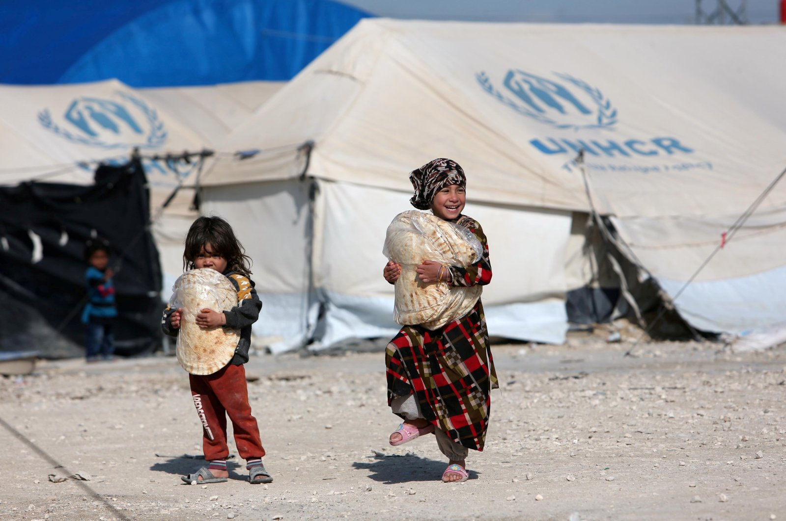 Children holding stacks of bread walk in an al-Hol displacement camp in Hassakeh governorate, Syria, April 2, 2019. (Reuters Photo)