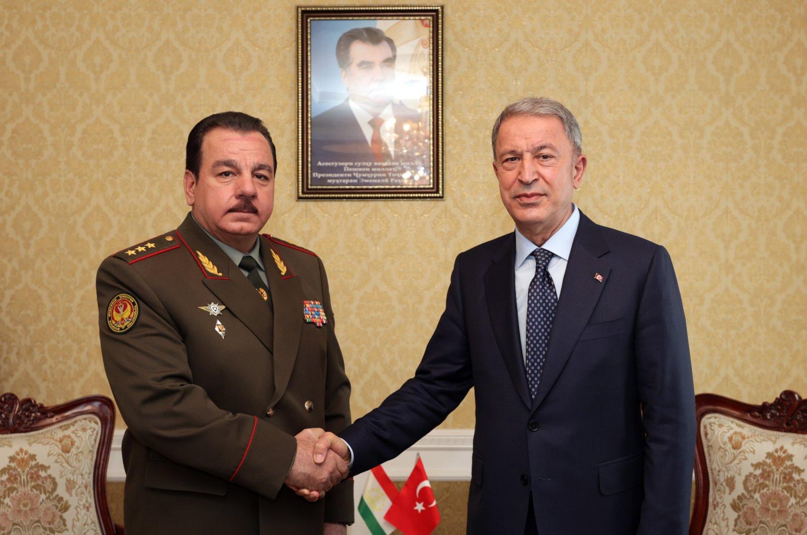 Turkey's Defense Minister Hulusi Akar (R) shakes hands with Tajik Counterpart Sherali Mirzo (L) in Dushanbe, Tajikistan, June 30, 2021. (AA Photo)