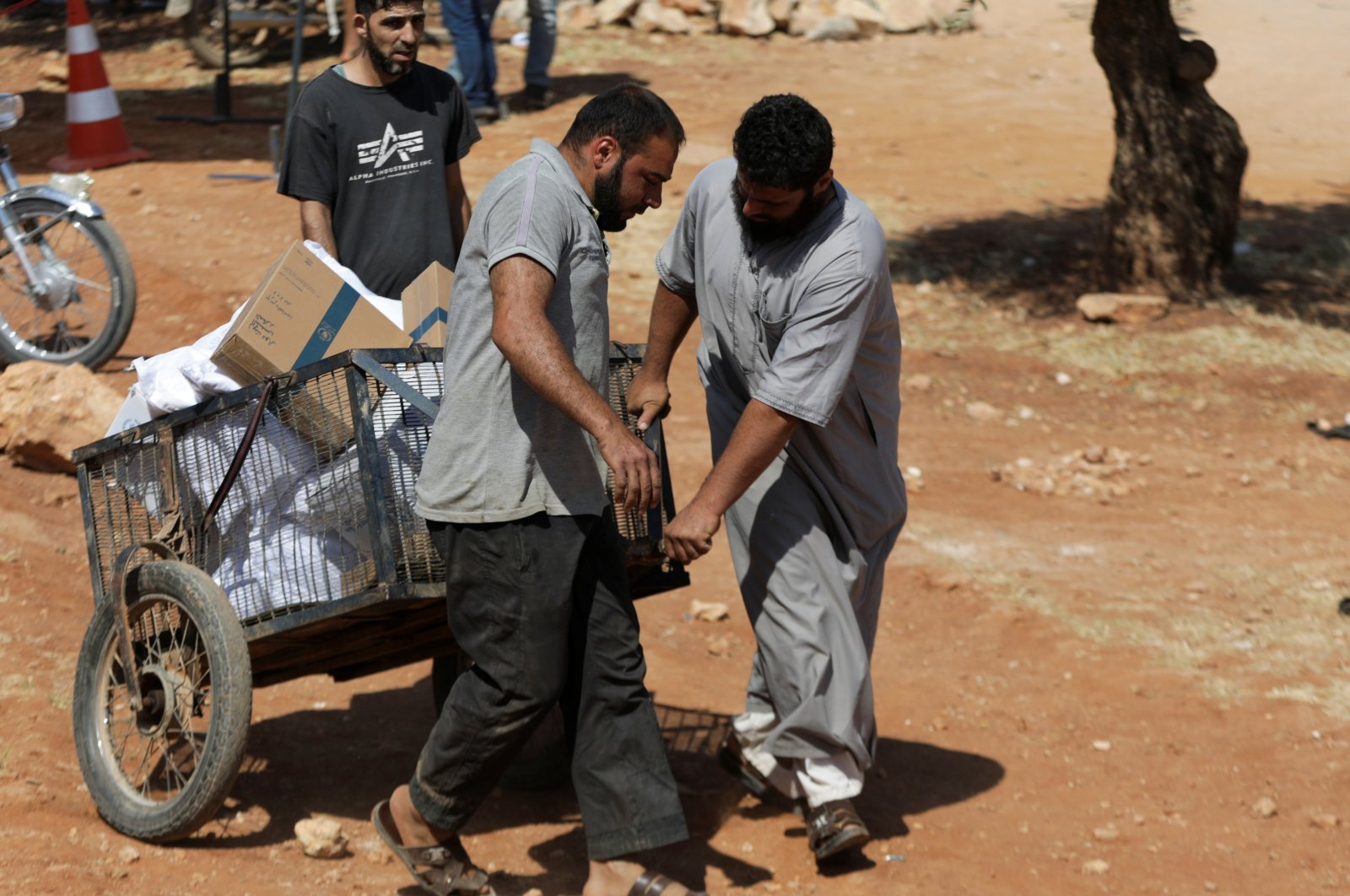 Internally displaced Syrian men pull a cart with humanitarian aid in the opposition-held Idlib, northwestern Syria, June 9, 2021. (REUTERS Photo)