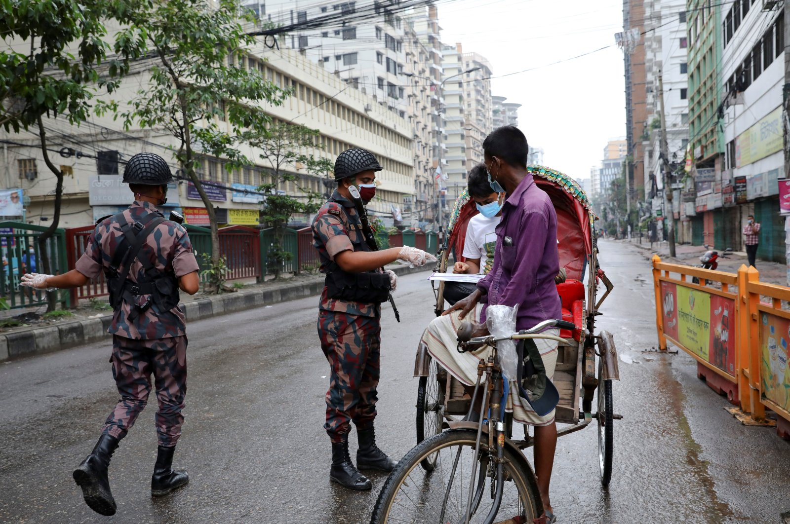 Members of Border Guard Bangladesh (BGB) check commuters at a checkpoint during a countrywide lockdown in Dhaka, Bangladesh, July 1, 2021. (Reuters Photo)