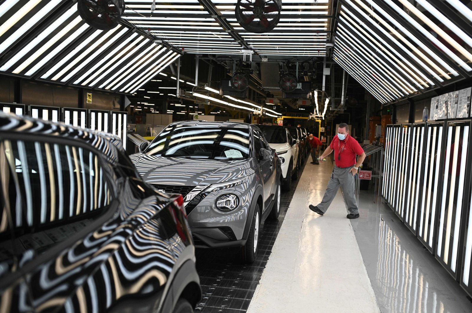 Nissan employees make final checks to cars on the production line at Nissan's plant in Sunderland, northeast England, July 1, 2021. (AFP Photo)