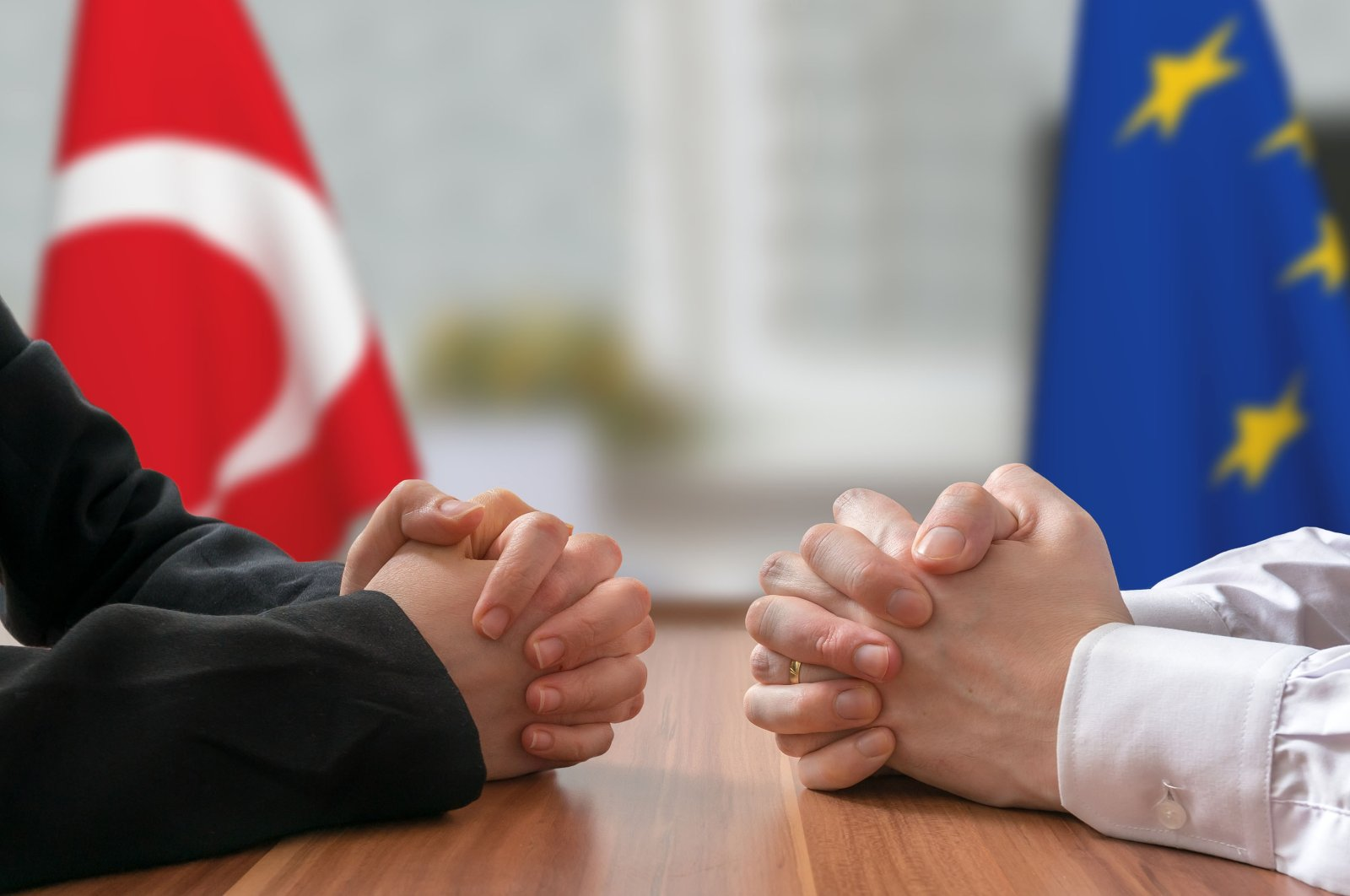Politicians with clasped hands in front of Turkish and European Union flags. (Shutterstock Photo)