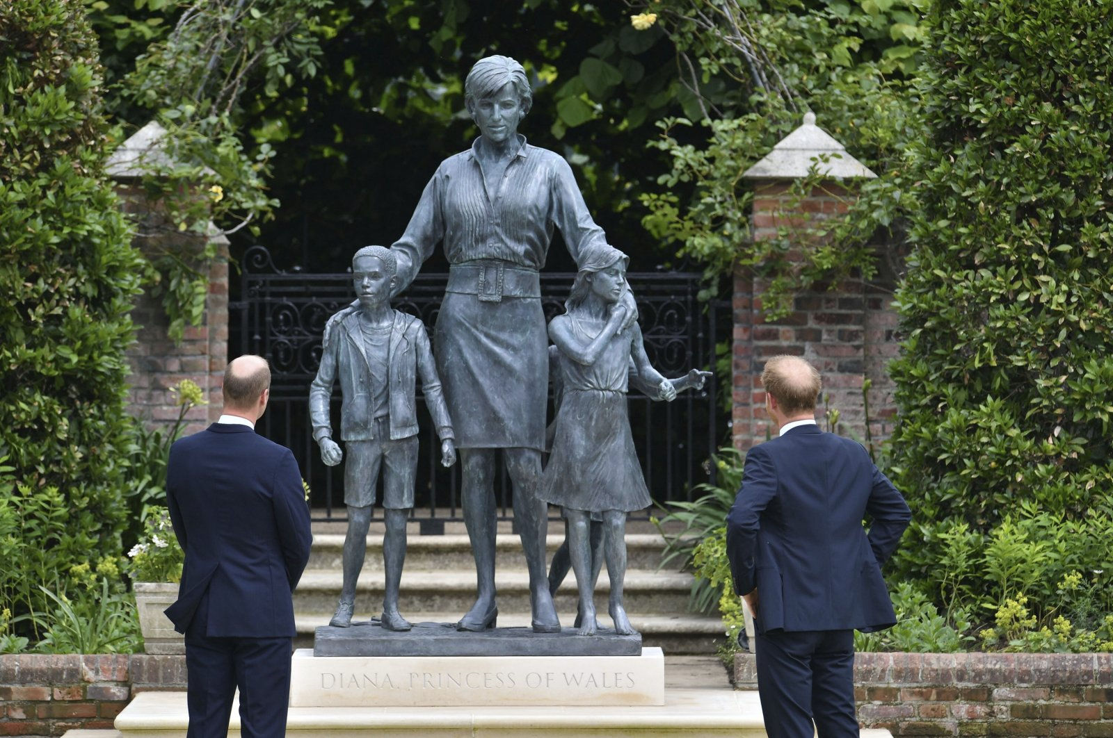 Britain's Prince William, (L) and Prince Harry unveil a statue they commissioned of their mother Princess Diana,  on what would have been her 60th birthday, in the Sunken Garden at Kensington Palace, London, U.K., July 1, 2021. (AP Photo)