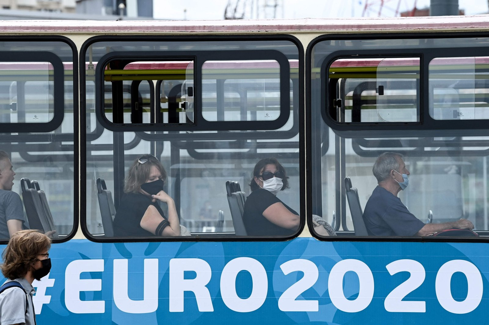 People, wearing a face mask amid the ongoing COVID-19 pandemic, sit in a tram in St. Petersburg, June 29, 2021. (AFP Photo)