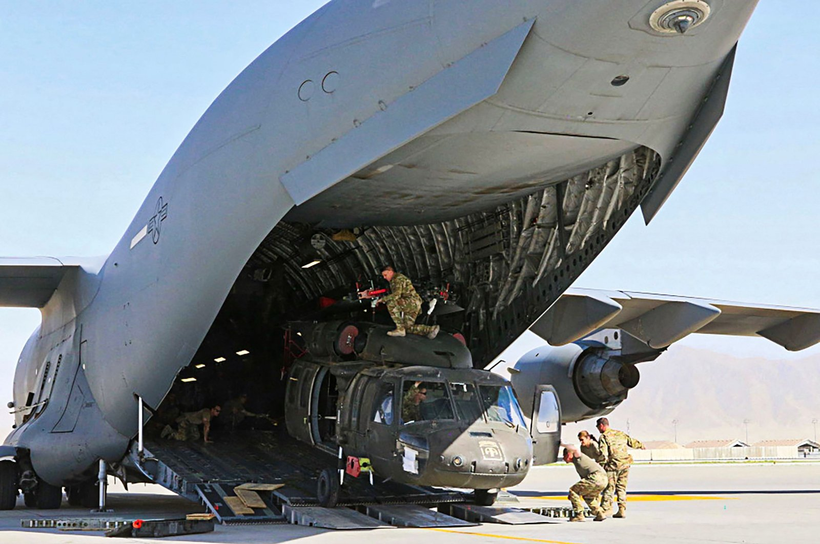 The U.S. Defense Visual Information Distribution Service (DVIDS) Aerial porters work with maintainers to load a UH-60L Blackhawk helicopter into a C-17 Globemaster III in support of the Resolute Support retrograde mission in Bagram, Afghanistan, June 29, 2021. (Photo by Sgt 1st Class Corey Vandiver/U.S. Defense Visual Information Distribution Service via AFP)