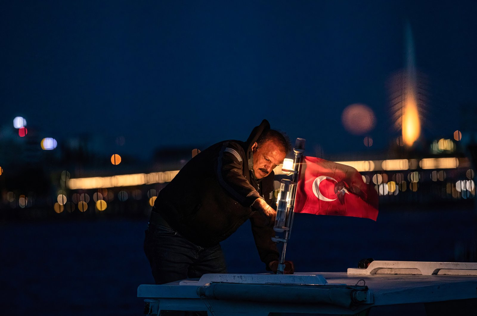 A man holds a Turkish flag on his boat on the Golden Horn coast of Istanbul, Turkey, May 26, 2021. (Photo by Getty Images)