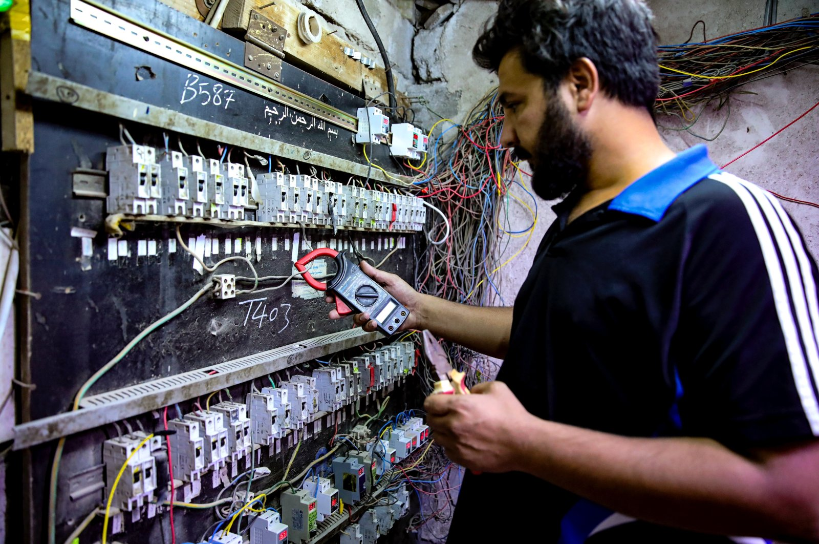 Kadim Aboud, a worker in a private electricity generating company, turns the switches to transfer electricity to private homes in Basra, Iraq, June. 29, 2021. (AP Photo)