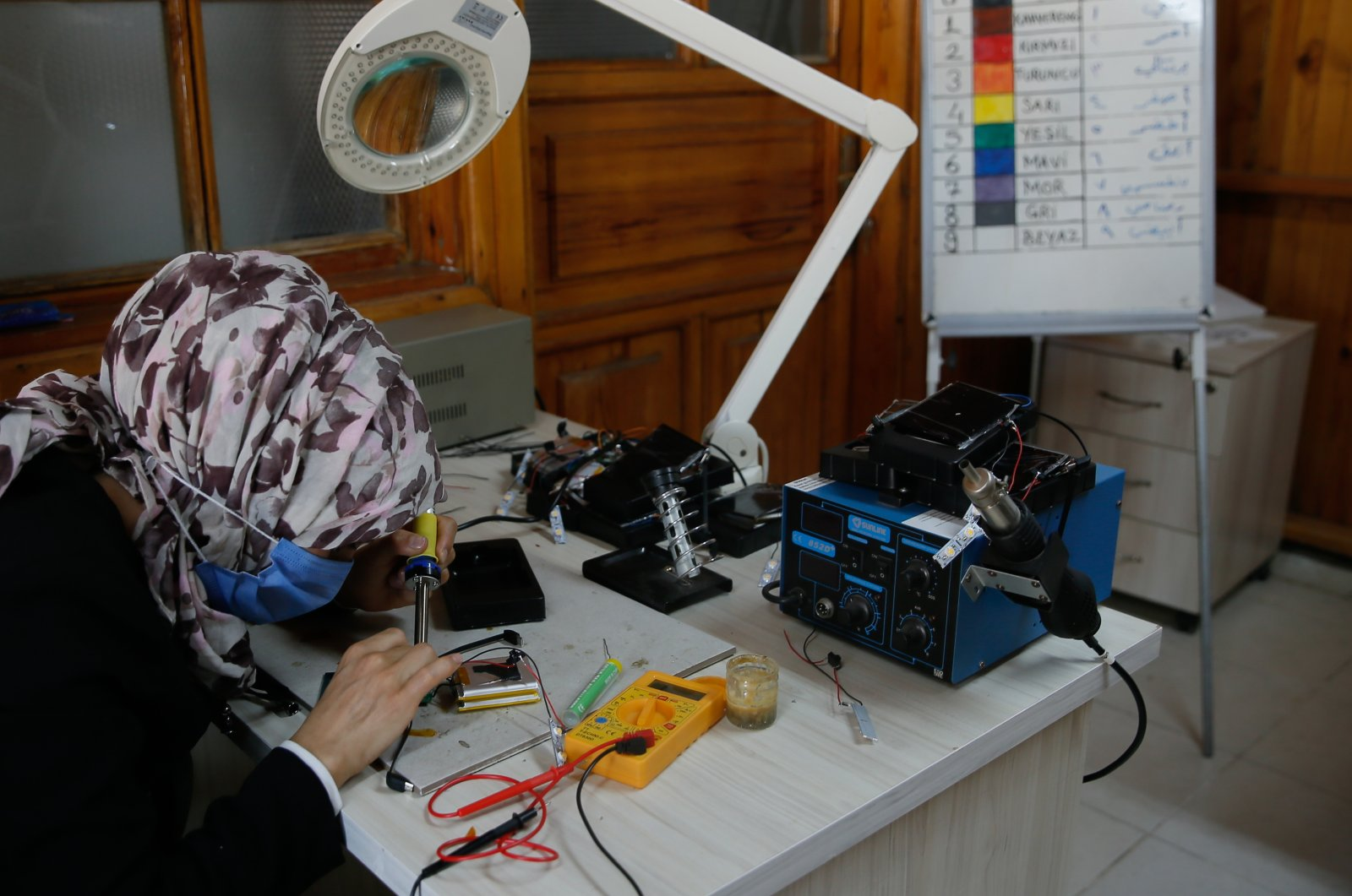 A woman builds a power bank in a workshop, in Izmir, western Turkey, July 2, 2021. (AA PHOTO)