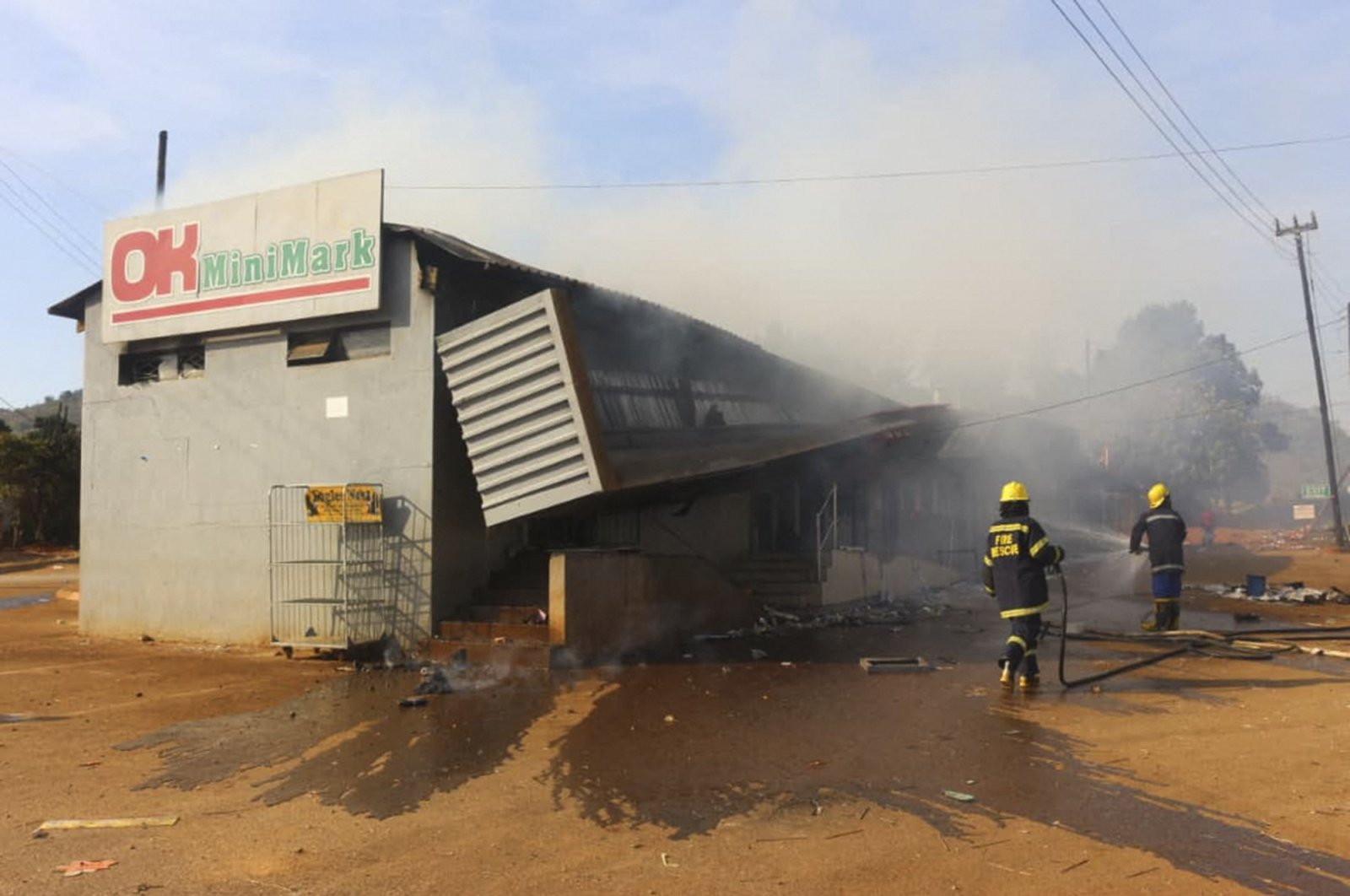 Firefighters extinguish a fire at a supermarket in Manzini, Eswatini, on June 30, 2021. (AFP Photo)
