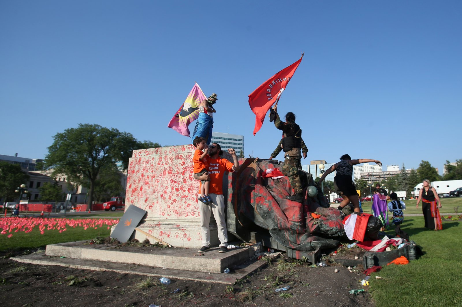 A defaced statue of Queen Victoria lies after being toppled during a rally, following the discovery of the remains of hundreds of children at former indigenous residential schools, outside the provincial legislature on Canada Day in Winnipeg, Manitoba, Canada, July 1, 2021. (Reuters Photo)