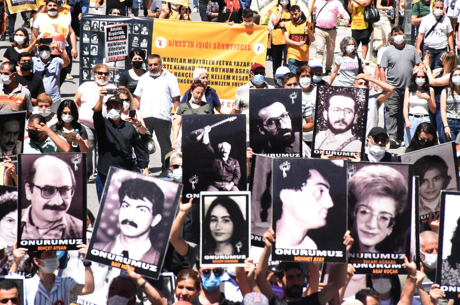 People hold pictures of the victims, during the commemoration ceremony in Sivas, central Turkey, July 2, 2021. (DHA PHOTO)