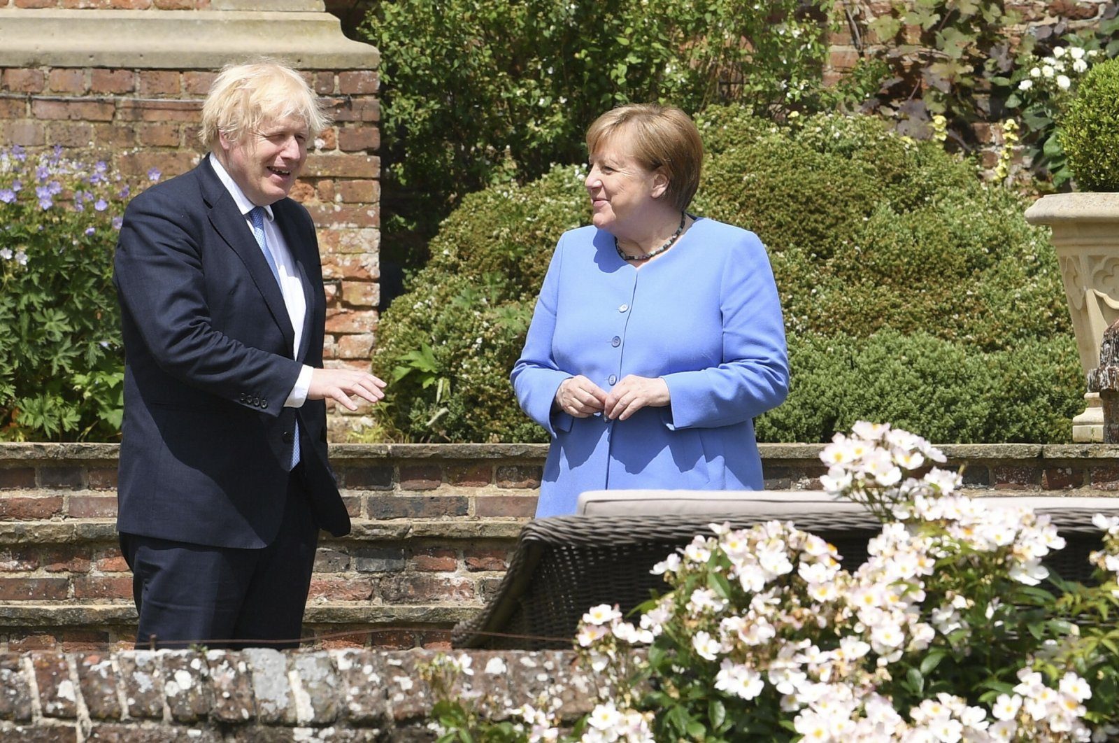 Britain's Prime Minister Boris Johnson (L) and German Chancellor Angela Merkel, walk through the garden at Chequers, the country house of the Prime Minister, in Buckinghamshire, England, July 2, 2021. (AP Photo)