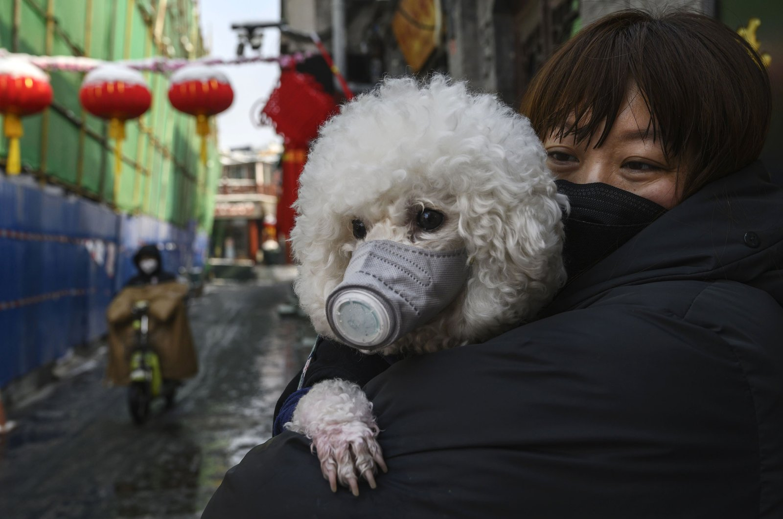 A Chinese woman holds her dog that is wearing a protective mask as they stand in the street in Beijing, China, Feb. 7, 2020. (Getty Images)