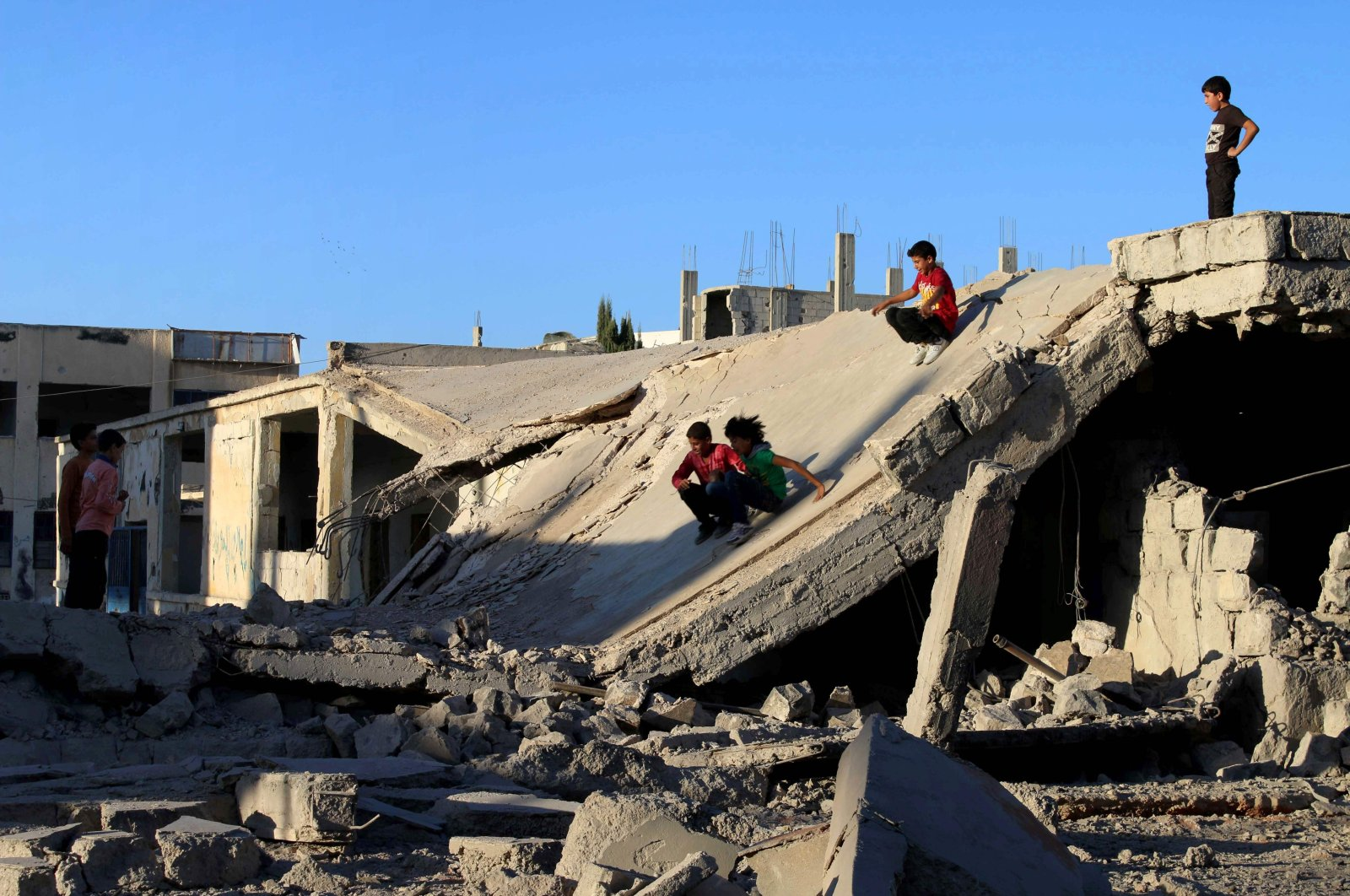 Syrian children slide down the rubble of destroyed a building in the opposition-held city of Daraa, in southwestern Syria, Sept. 12, 2016. (AFP File Photo)