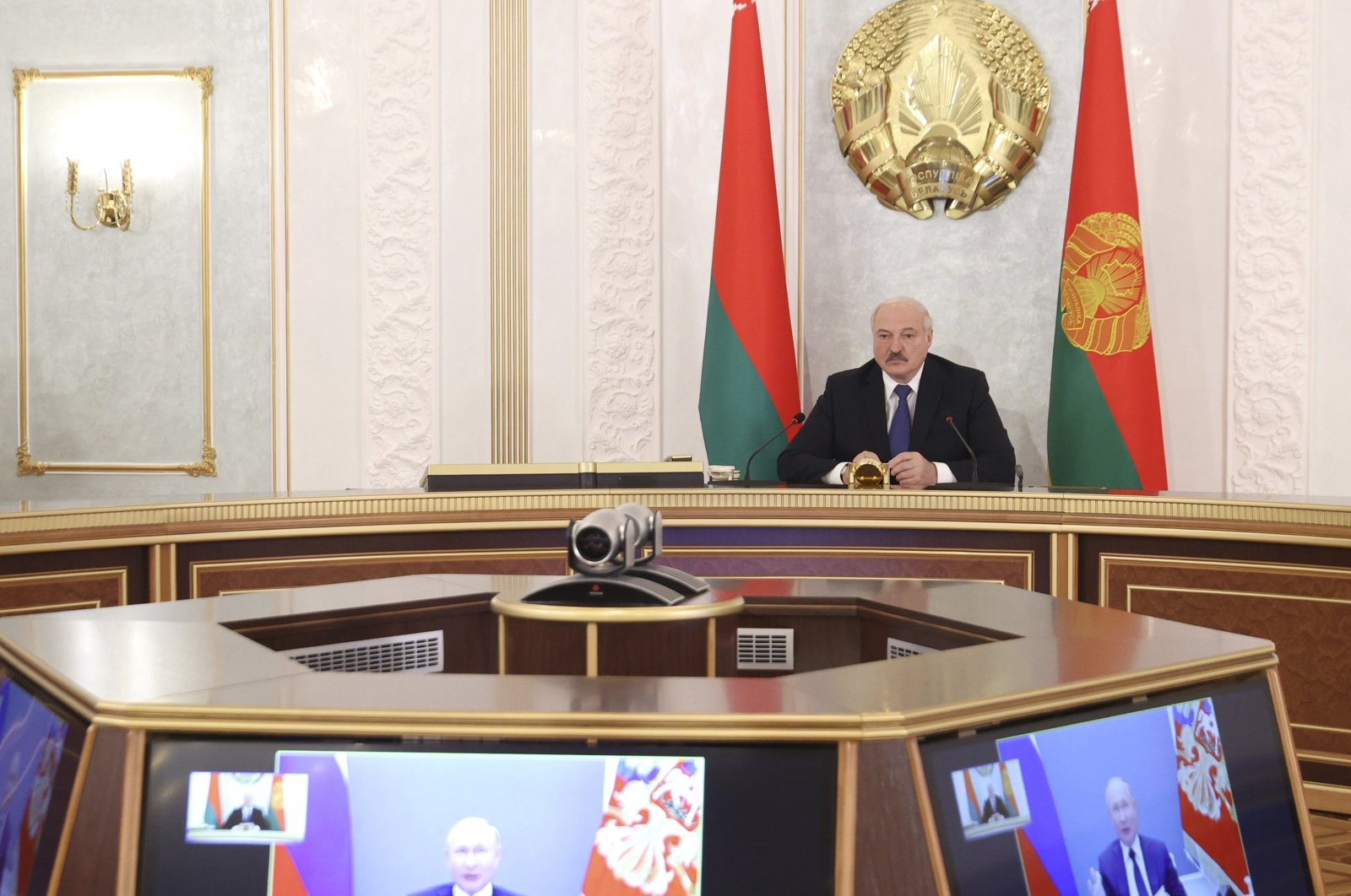 Belarusian President Alexander Lukashenko takes part in a video call with Russian President Vladimir Putin, on the screens, and Russian and Belarusian officials in Minsk, Belarus, Thursday, July 1, 2021. (AP Photo)
