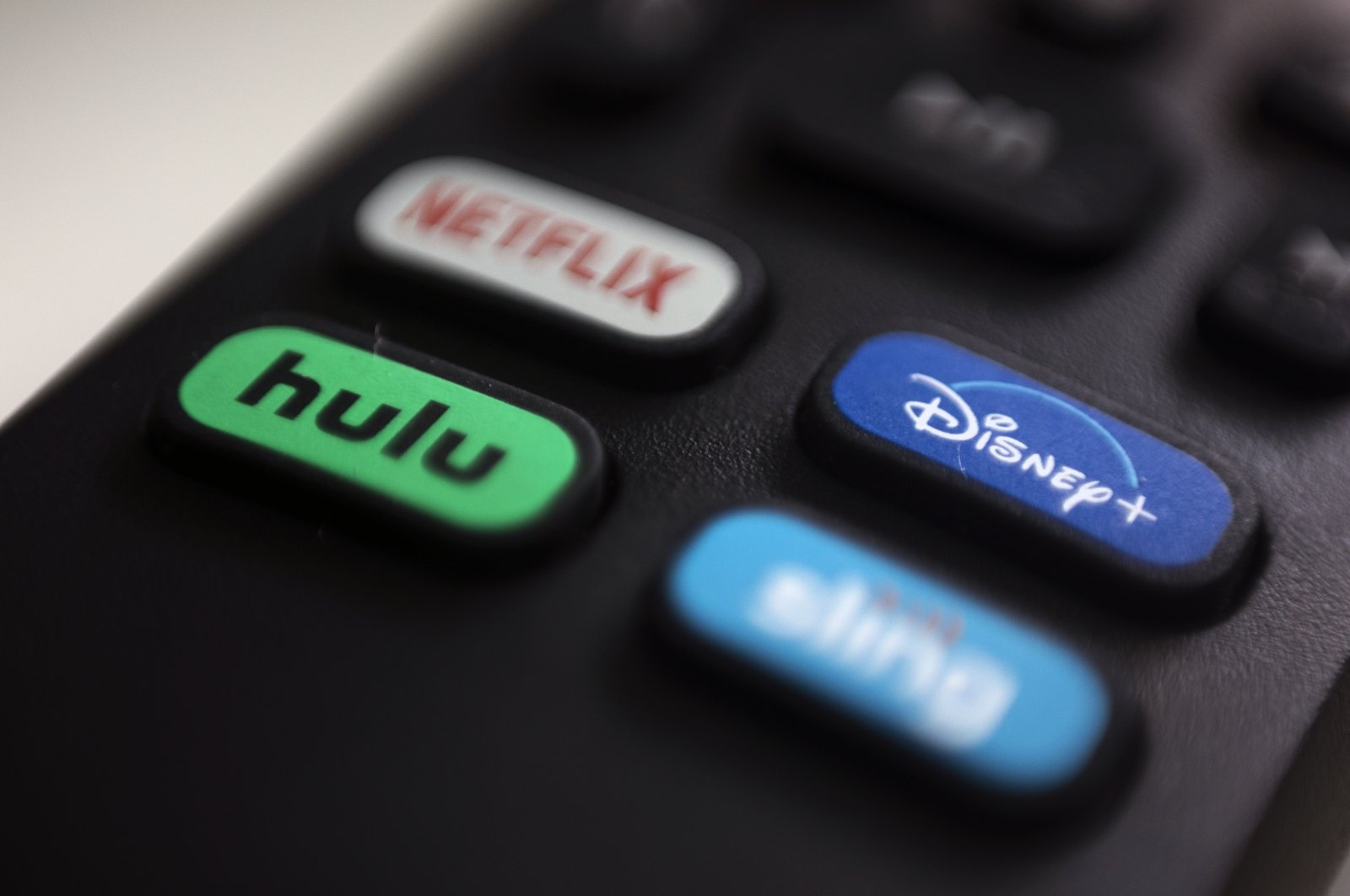 The logos for Netflix, Hulu, Disney Plus and Sling TV are pictured on a remote control in Portland, Oregon, U.S., Aug. 13, 2020.  (AP Photo)