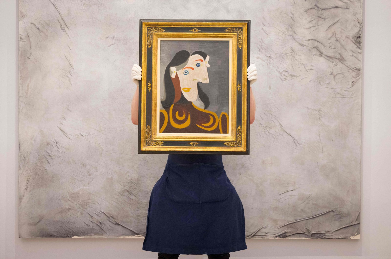 """A gallery worker poses with an artwork entitled """"Buste de femme a la robe brune"""" (Bust of a woman in a brown dress) by Spanish painter Pablo Picasso during a photocall at Sotheby's auction house in central London, U.K., June 22, 2021. (Tolga Akmen via AFP)"""