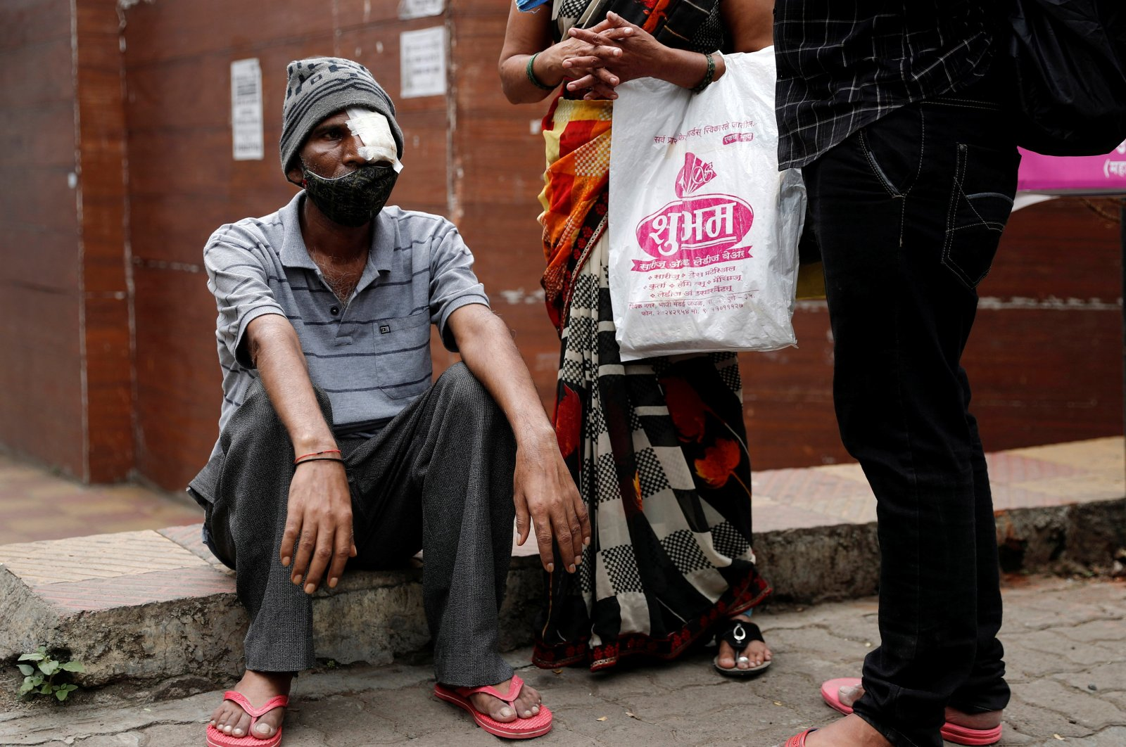 Shivaji Veer (L), 51, a school bus driver, accompanied by his wife Vimal Veer 46, waits to board a taxi to go home after a follow-up consultation at a hospital after losing his eye due to Mucormycosis, also known as black fungus, in Pune, India, July 1, 2021. (Reuters Photo)
