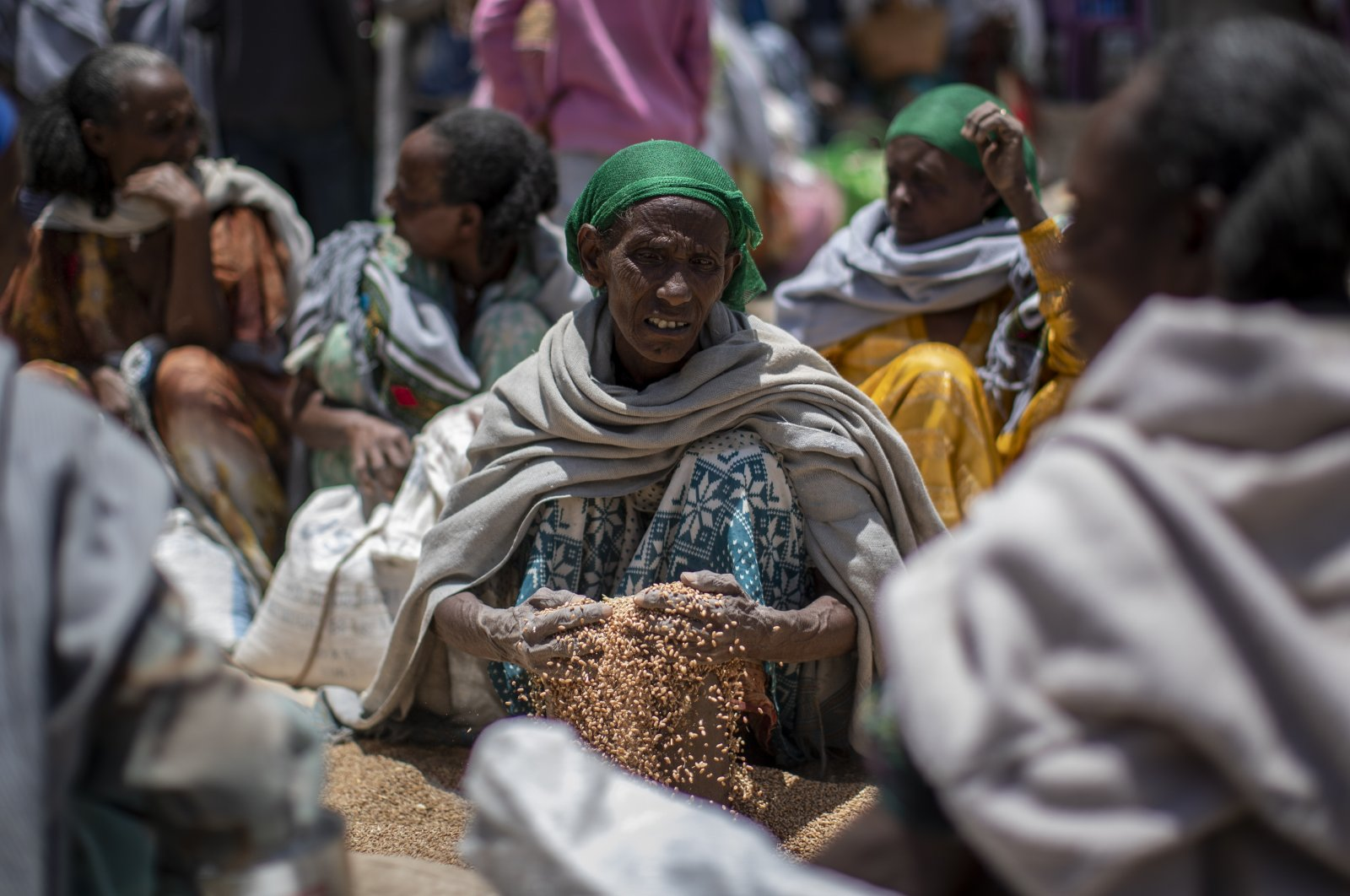 An Ethiopian woman scoops up grains of wheat after it was distributed by the Relief Society of Tigray in the town of Agula, in the Tigray region of northern Ethiopia, May 8, 2021. (AP Photo)