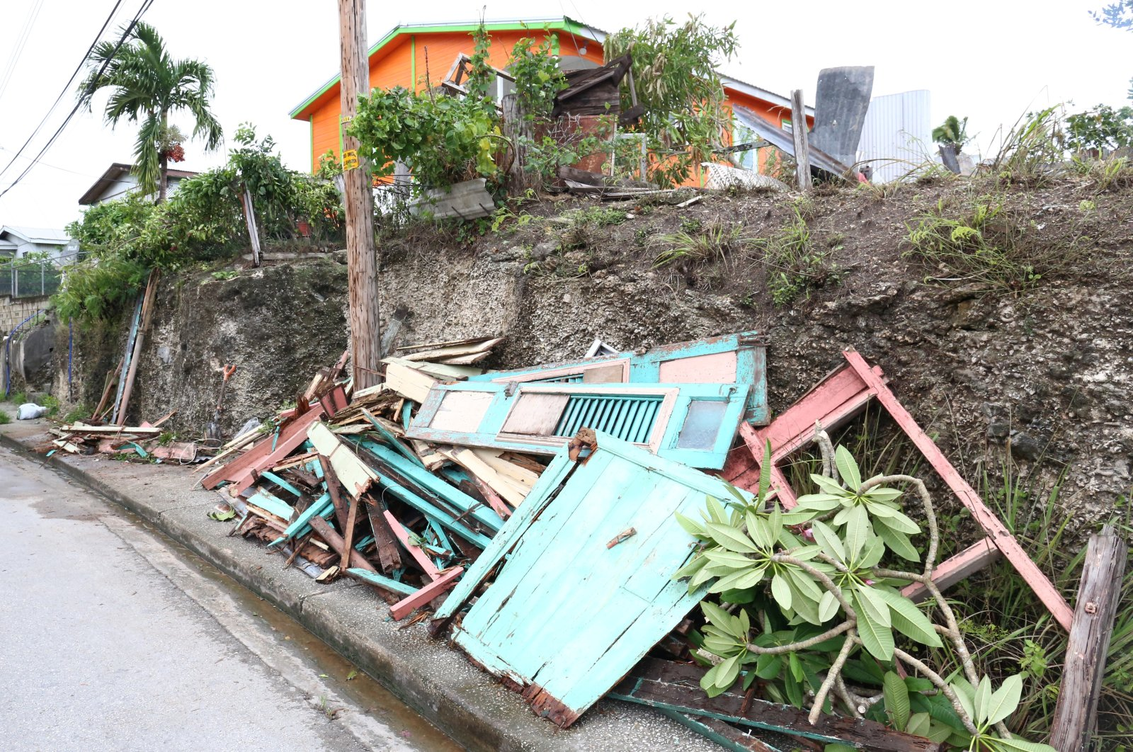 Debris from a house lies next to a road after strong winds of Hurricane Elsa passed St. Michael, Barbados, July 2, 2021.  (Reuters Photo)