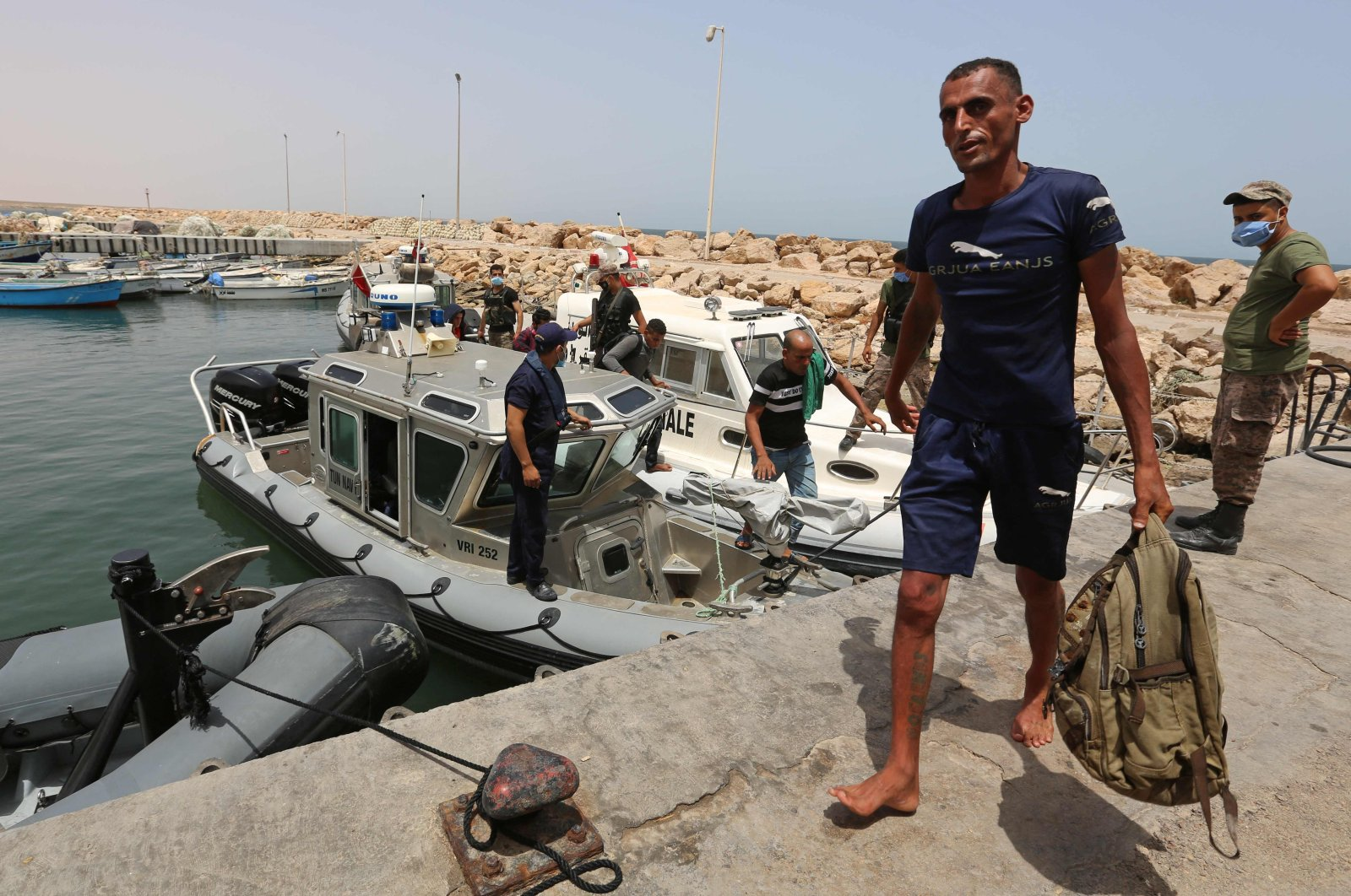 Migrants rescued by Tunisia's national guard during an attempted crossing of the Mediterranean by boat, arrive at the port of el-Ketef in Ben Guerdane in southern Tunisia near the border with Libya, June 27, 2021. (AFP Photo)
