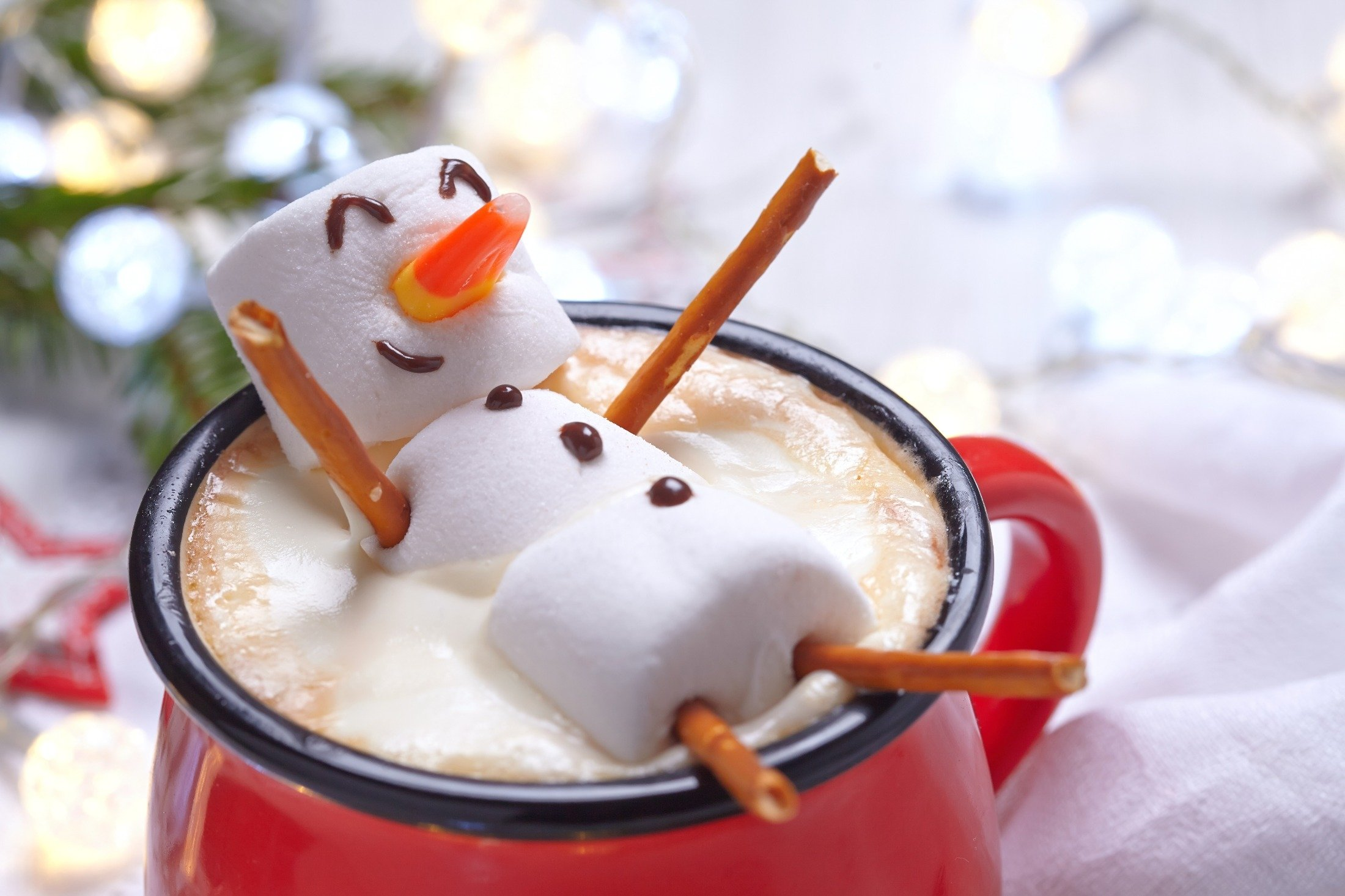 A melting marshmallow snowman rests atop hot chocolate in a red cup. (Shutterstock Photo)