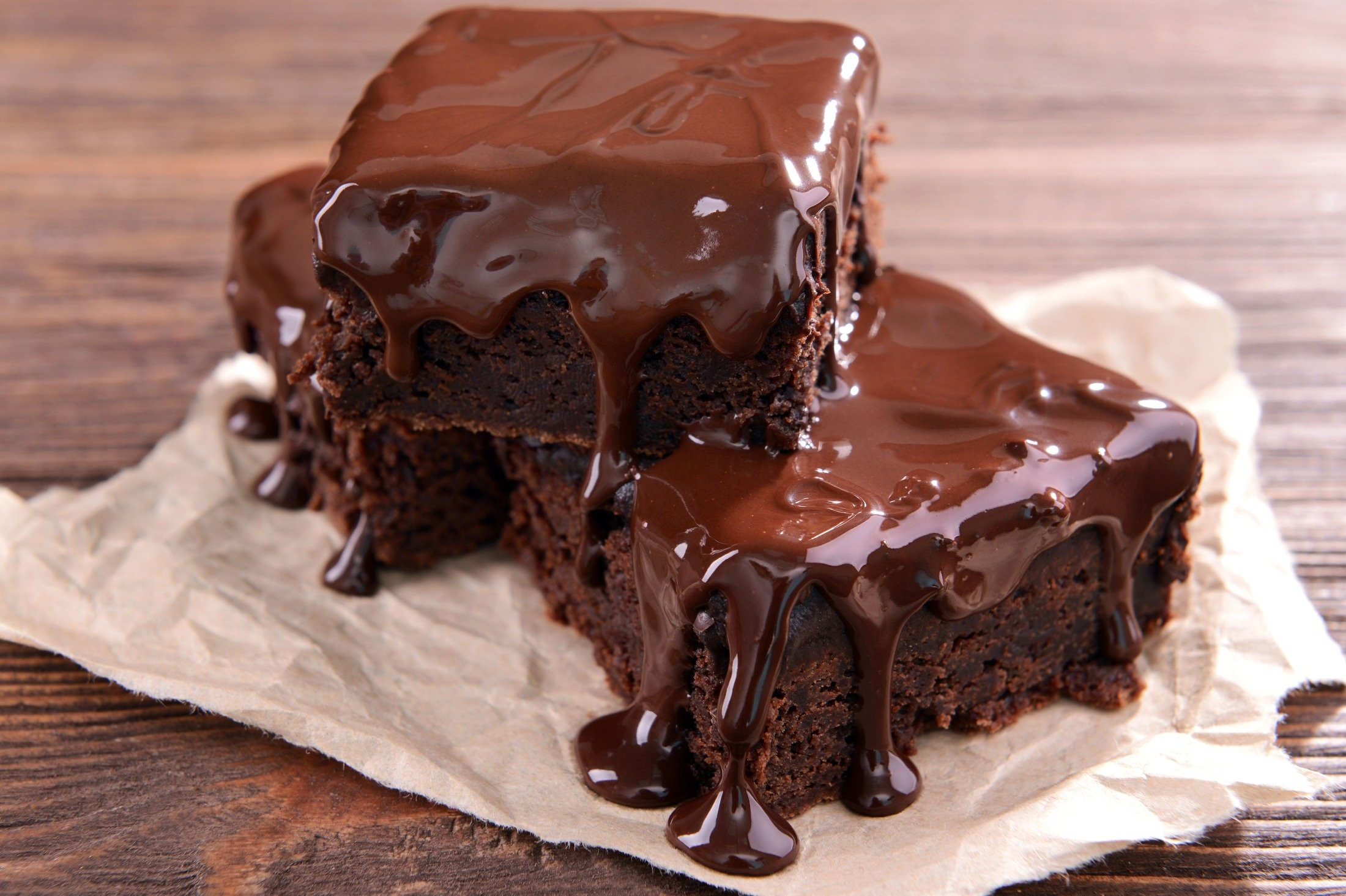 Chocolate topping drips from the edges of cakes on a table. (Shutterstock Photo)