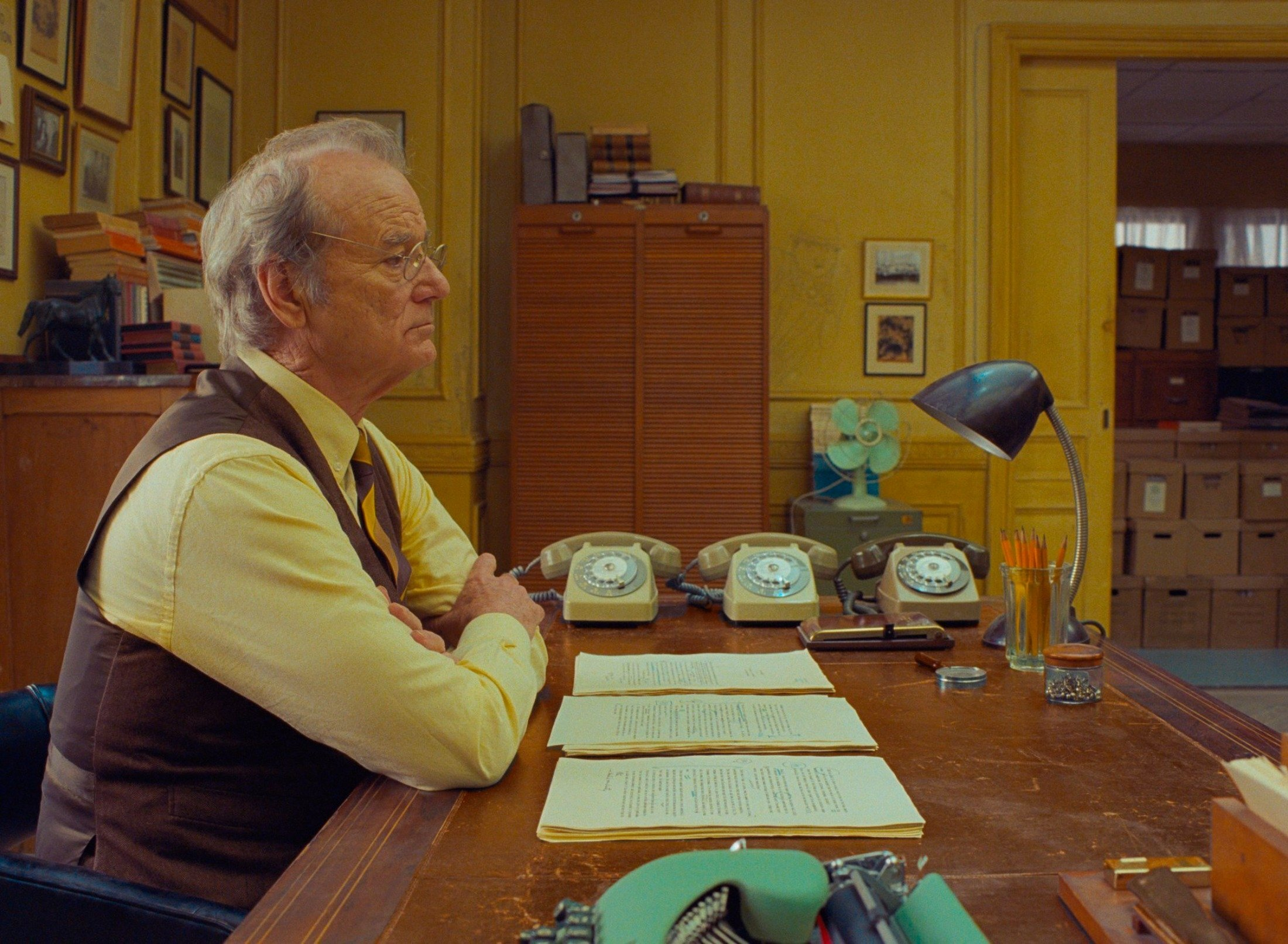 Bill Murray sits behind a desk in a scene from Wes Anderson's film 'The French Dispatch.' (Searchlight Pictures via AP)