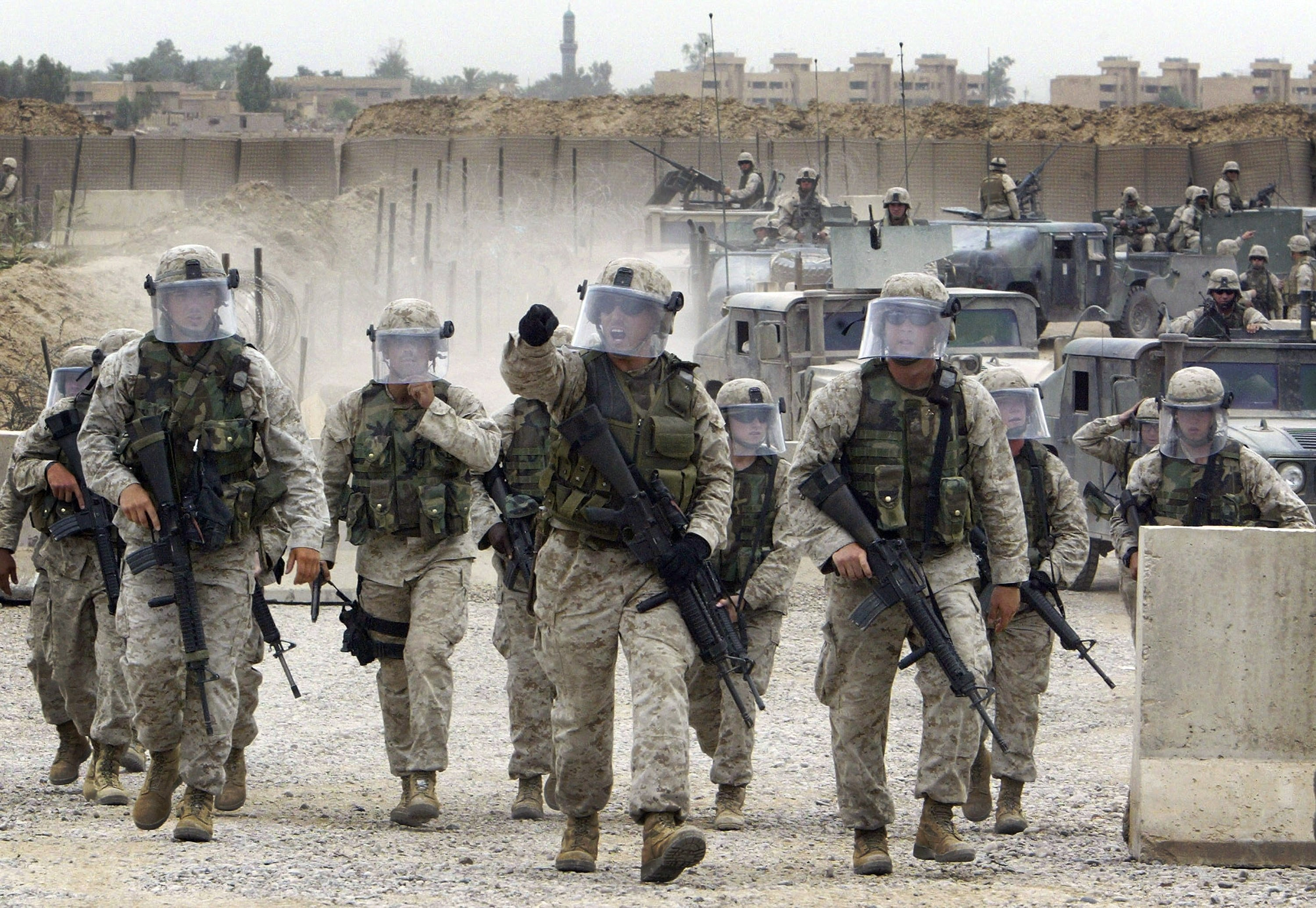 U.S. soldiers rush to escort a convoy of prisoners released from the Abu Ghraib facility in Baghdad, Iraq, May 28, 2004. (AP Photo)