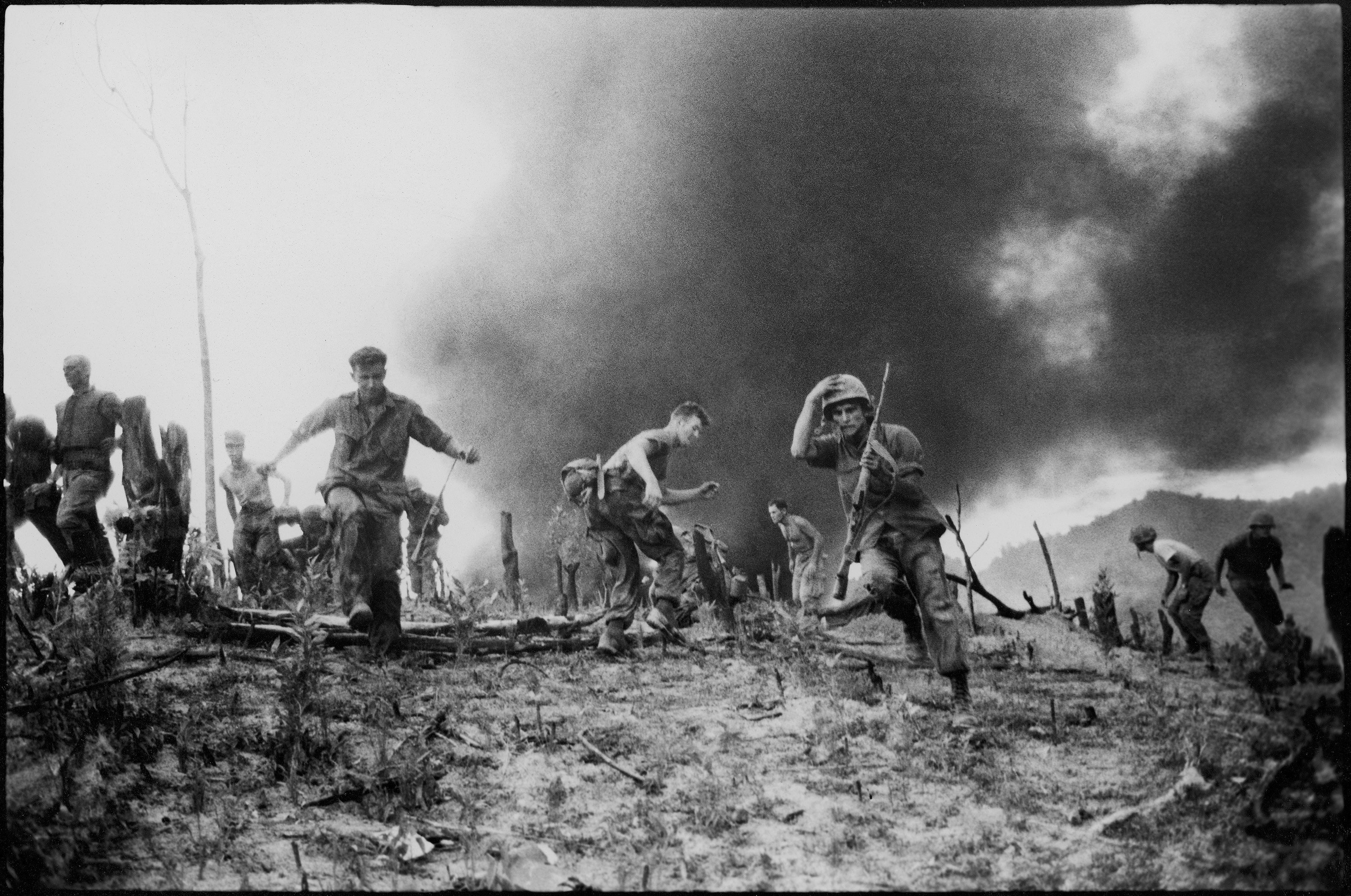 U.S. Marines scatter as a CH-46 helicopter burns, background, after it was shot down near the demilitarized zone (DMZ) between North and South Vietnam, July 15, 1966. (AP Photo)