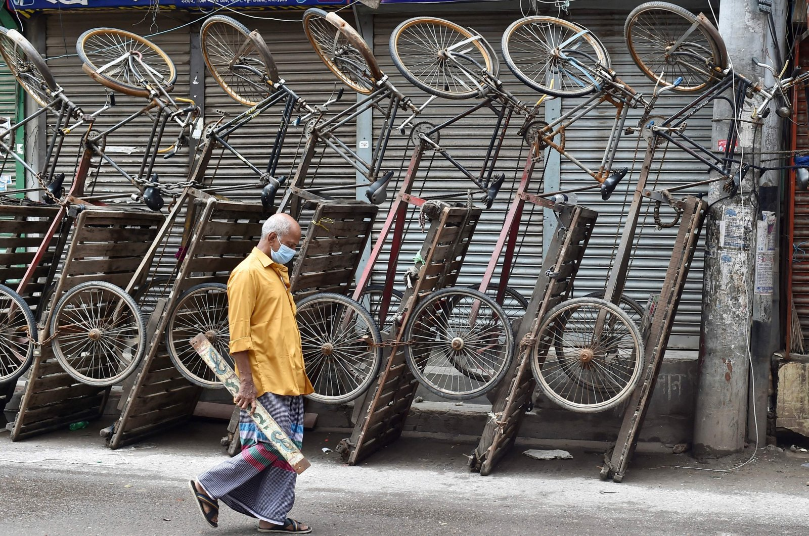 A man walks past parked bicycle carts along a street in Dhaka, Bangladesh, July 3, 2021. (AFP Photo)