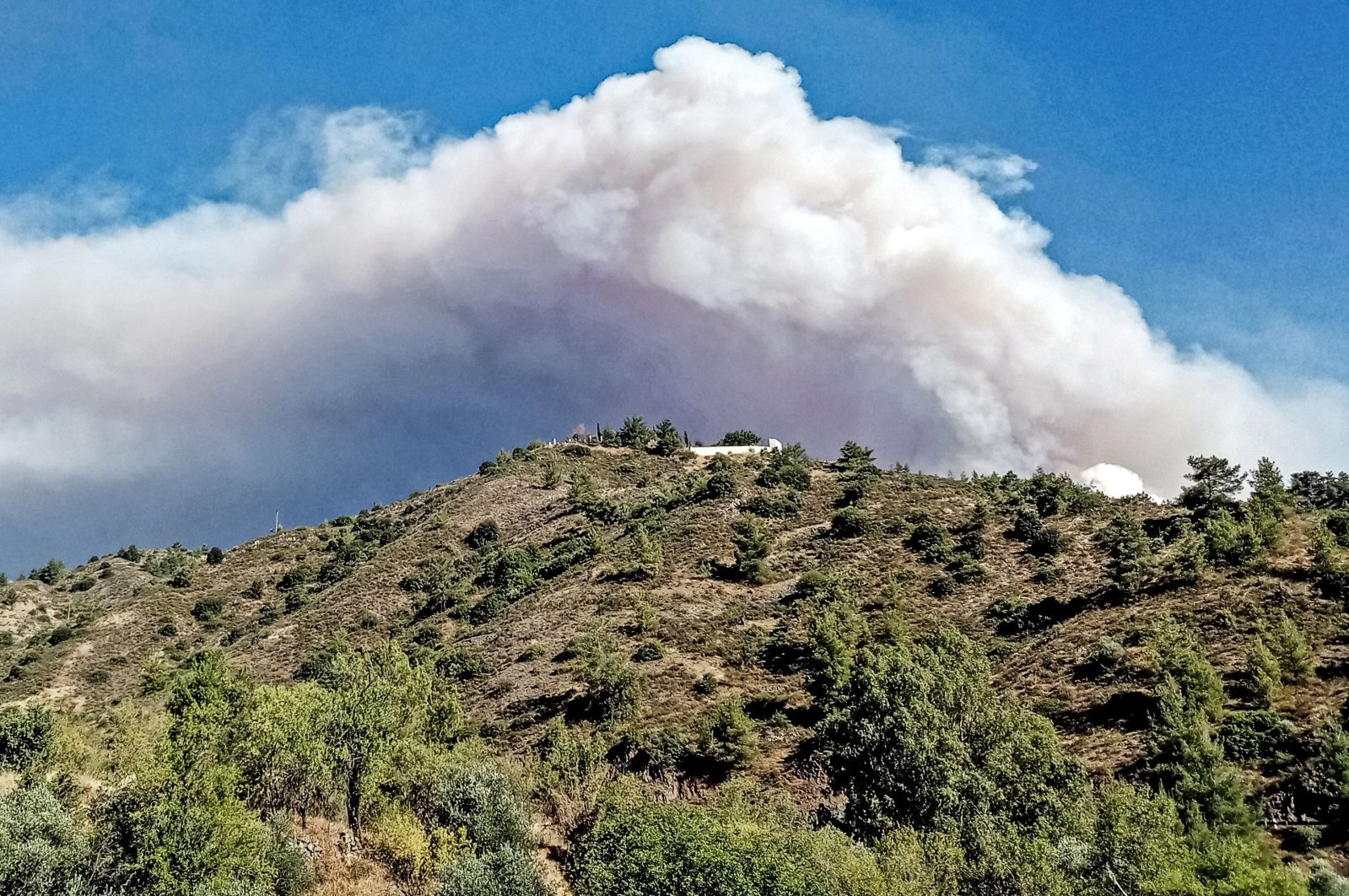A picture taken from near the village of Farmakas in the Nicosia district of Greek Cyprus, shows heavy smoke billowing from behind the mountains as a giant fire rages in the Larnaca district of the island, on July 3, 2021. (AFP Photo)