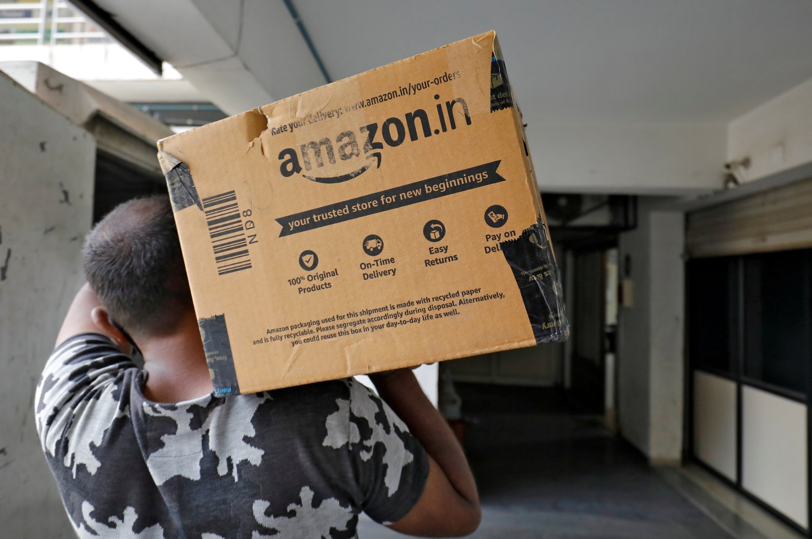 A delivery worker carries an Amazon package to deliver it to a customer at a residential apartment in Ahmedabad, India, March 17, 2021. (Reuters Photo)