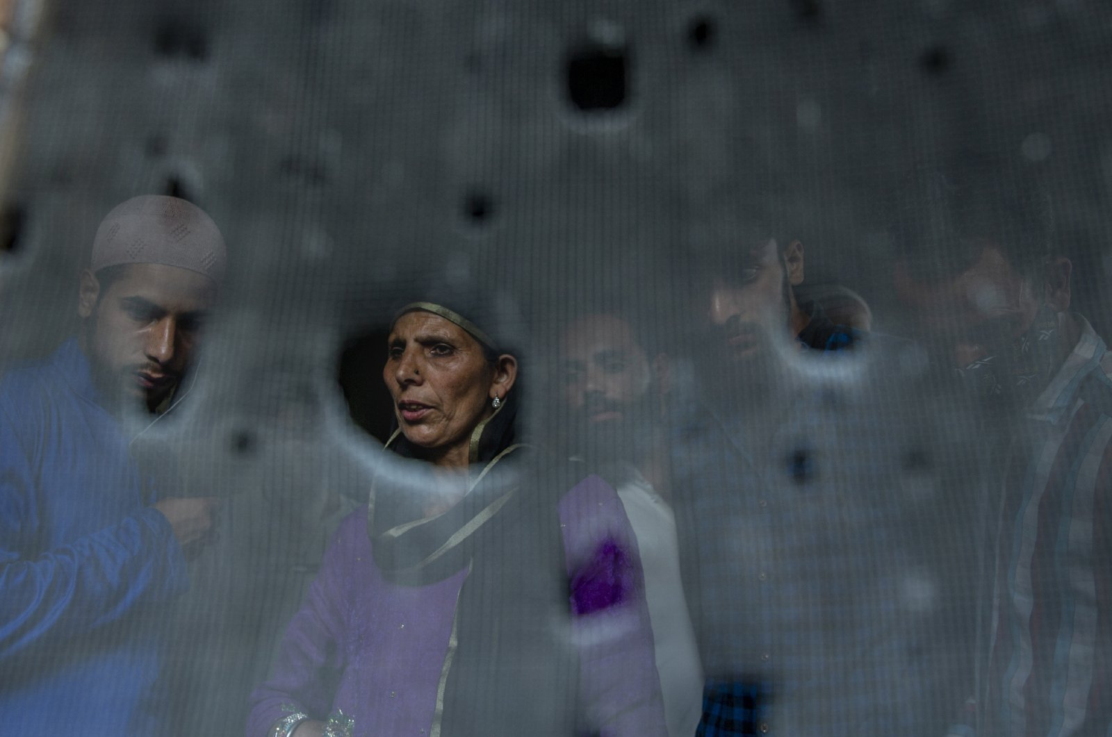 Kashmiri villagers are seen through the bullet-ridden iron mesh of a window of the residential house where suspected rebels were taking refuge, after a gunfight in Pulwama, south of Srinagar, Indian controlled Kashmir, Friday, July 2, 2021. (AP Photo)