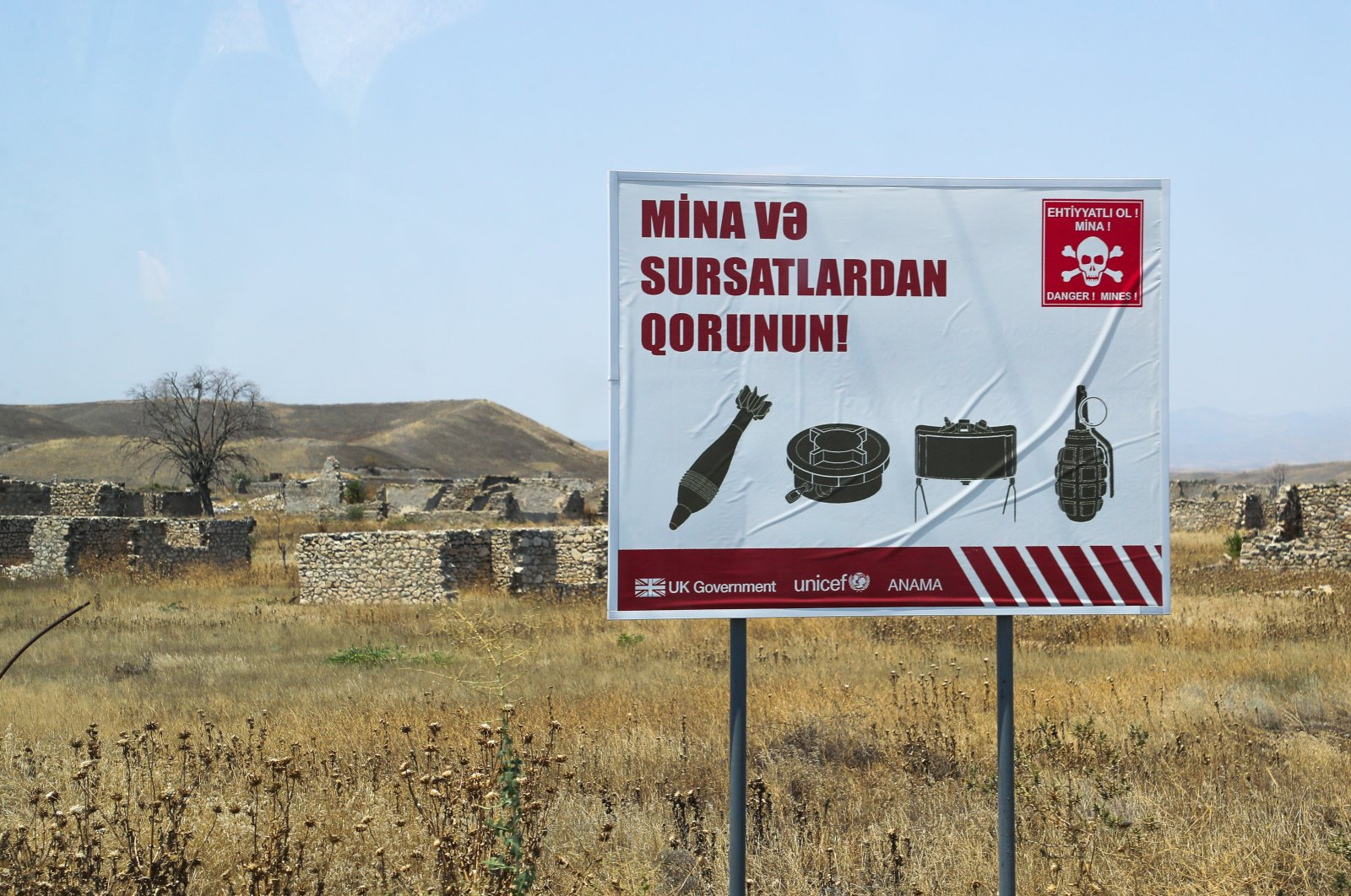 A sign warning of mines and ammunition is seen in the Zangilan district, where the Smart Village pilot project is being implemented, Azerbaijan, July 3, 2021. (Getty Images)