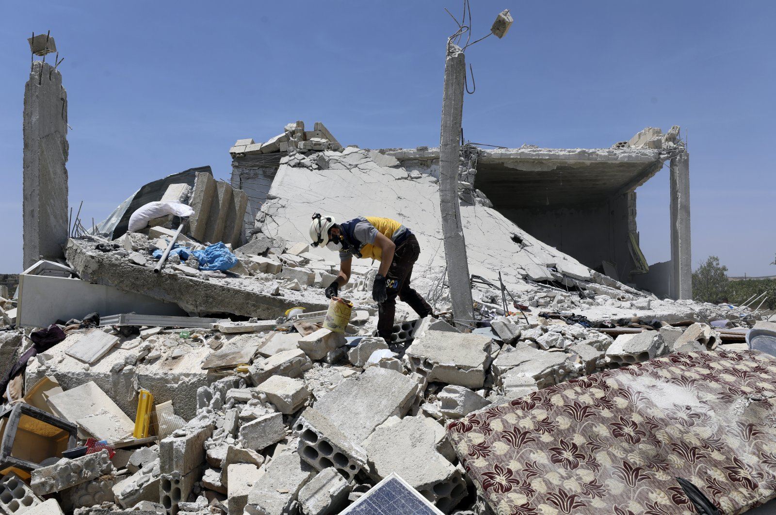 A civil defense worker inspects a damage house after shelling hit the town of Ibleen, a village in southern Idlib province, Syria, Saturday, July 3, 2021. (AP Photo)