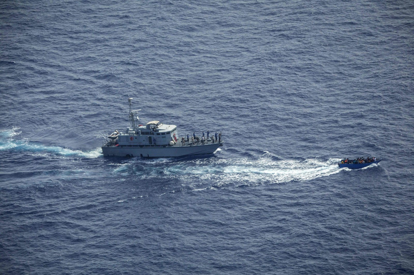 """This handout aerial image taken by German NGO """"Sea-Watch"""" shows the Libyan coast guard (L) near a migrant boat in the Malta Search and Rescue Zone, June 30, 2021. (AFP Photo)"""