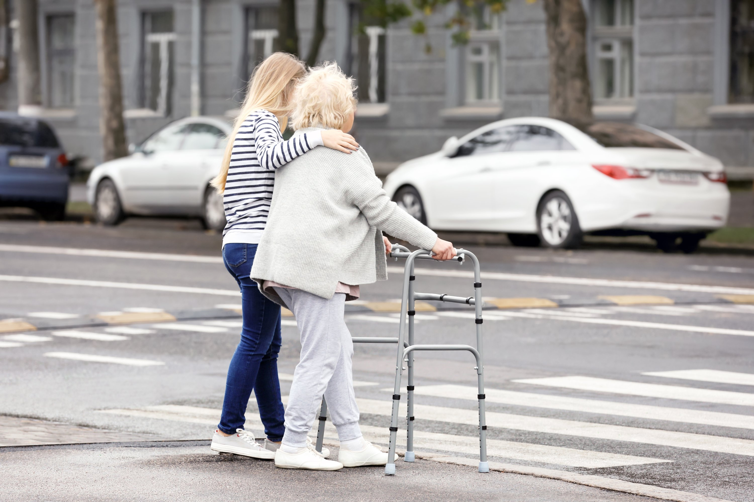 A young woman helps her elderly grandmother cross the road. (Shutterstock Photo)