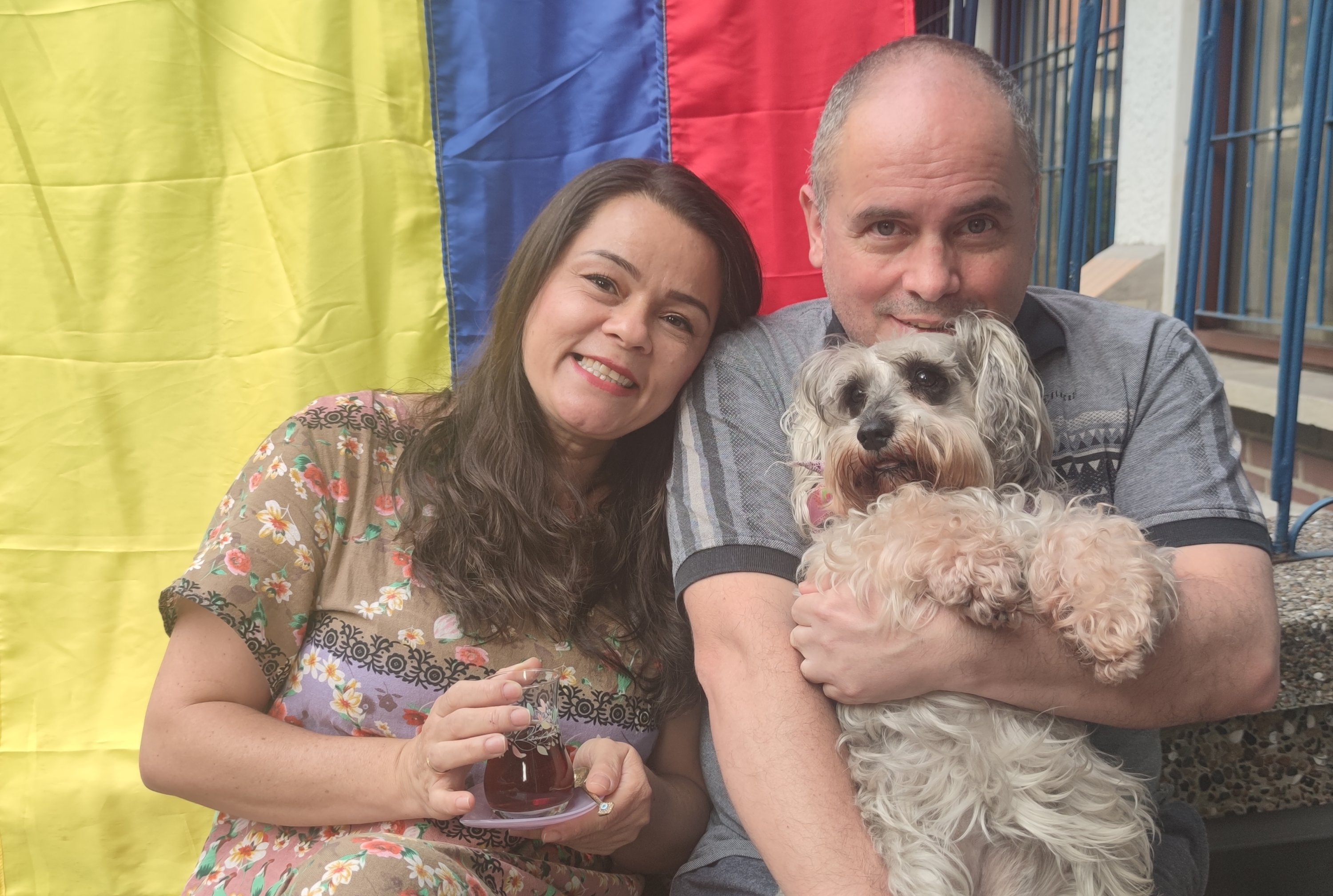 Dioni Martinez (L) poses with her husband and their dog, holding a glass of Turkish tea in their house in Medellin, Colombia, July 3, 2021. (AA Photo)