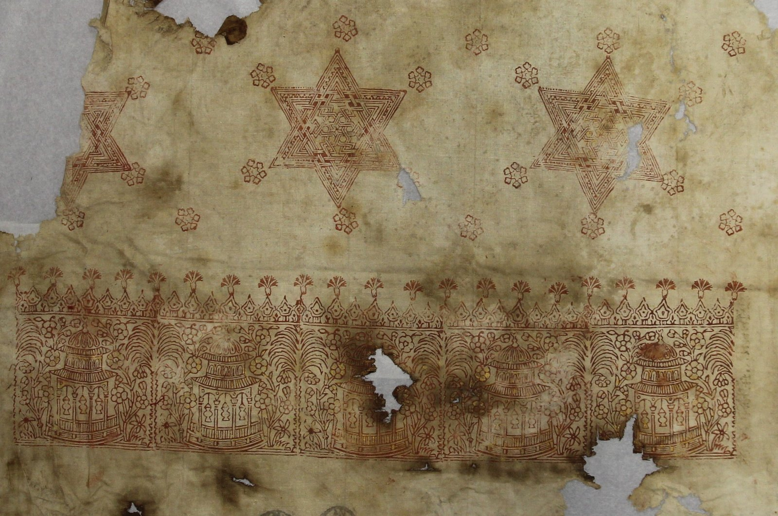 Textile with small kiosks and palm trees and strap-work stars, linen, block printed, with applied gold foil and two inspection seals, from Ottoman Egypt, 1600s or 1700s. (Courtesy of Bolton Library and Museum Services)