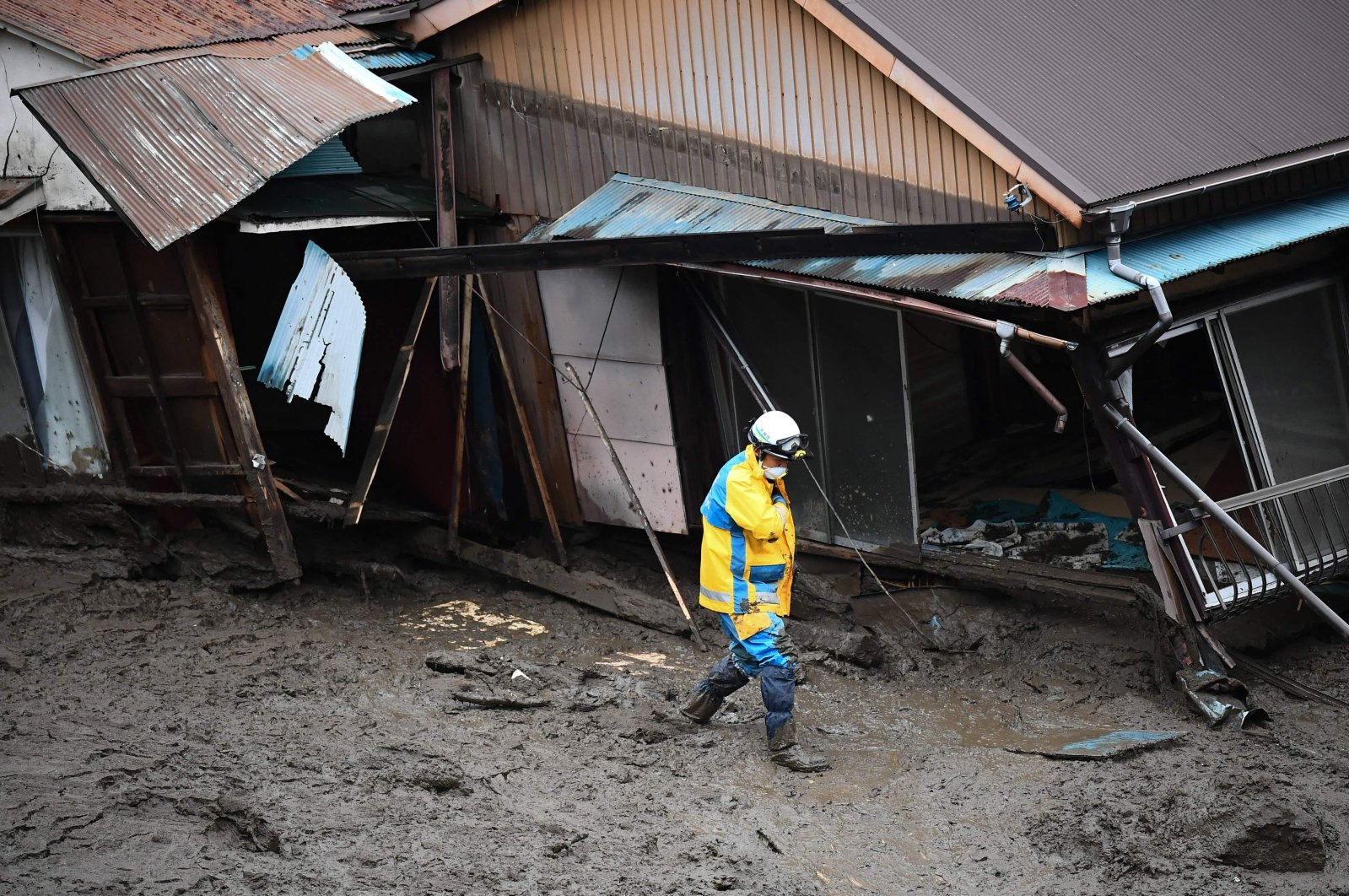 A police officer walks through the mud past a damaged building at the scene of a landslide in Atami, Shizuoka Prefecture, Japan, July 5, 2021. (AP Photo)