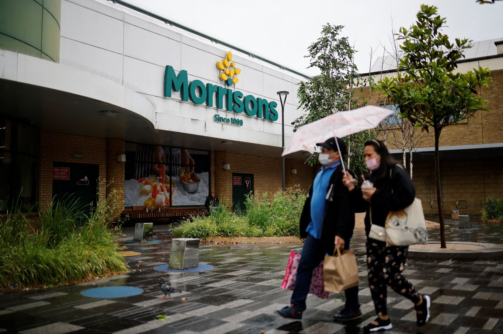 People walk past a Morrisons supermarket in Stratford, east London, June 21, 2021. (AFP Photo)