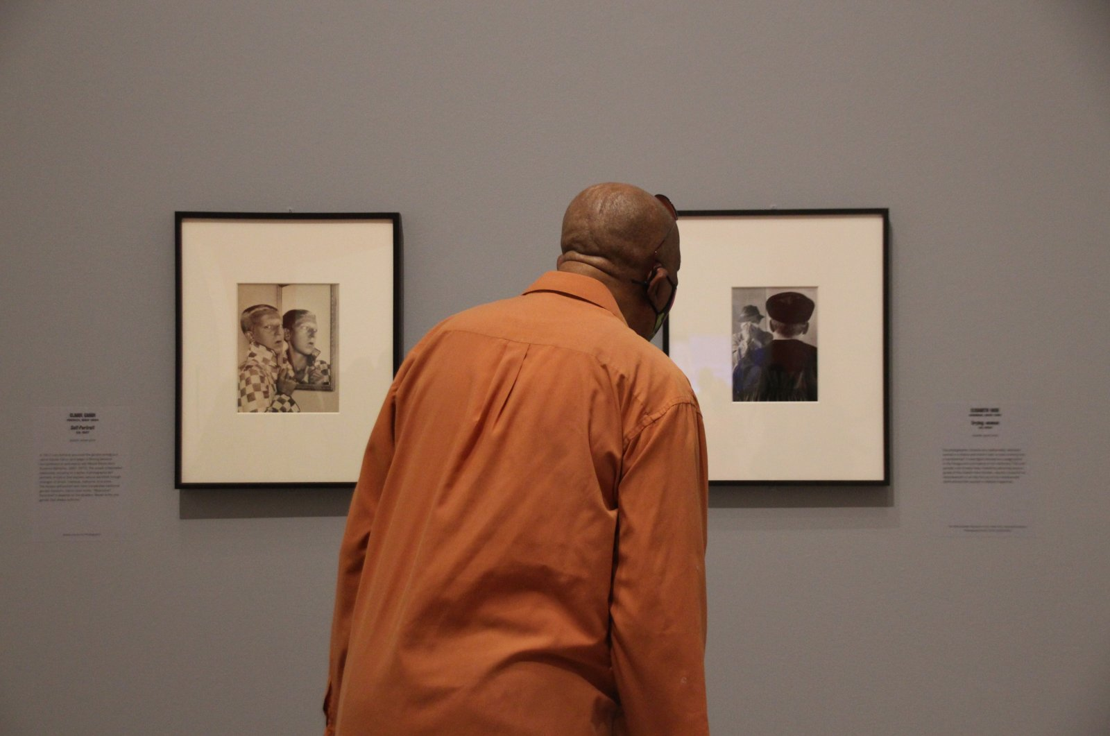 """A visitor stands in front of two exhibits, """"Self-portrait"""" by Claude Cahun (L) and """"Crying woman"""" by Elisabeth Hase, at the exhibition """"The New Woman Behind The Camera"""" at New York's Met Museum. (DPA Photo)"""