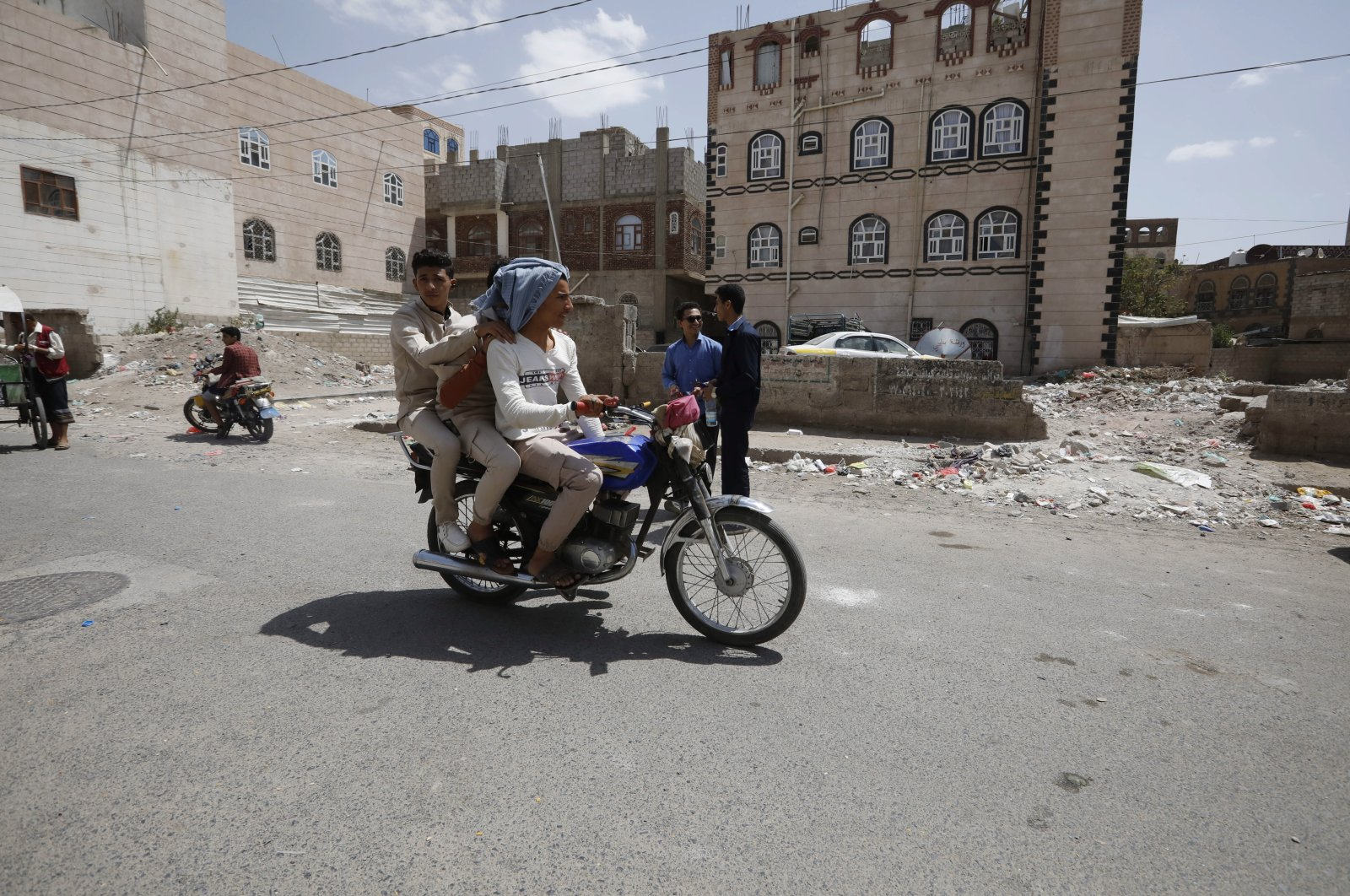 Yemeni students riding a motorcycle leave a public school after taking final school exams in Sanaa, Yemen, July 5, 2021. (EPA Photo)