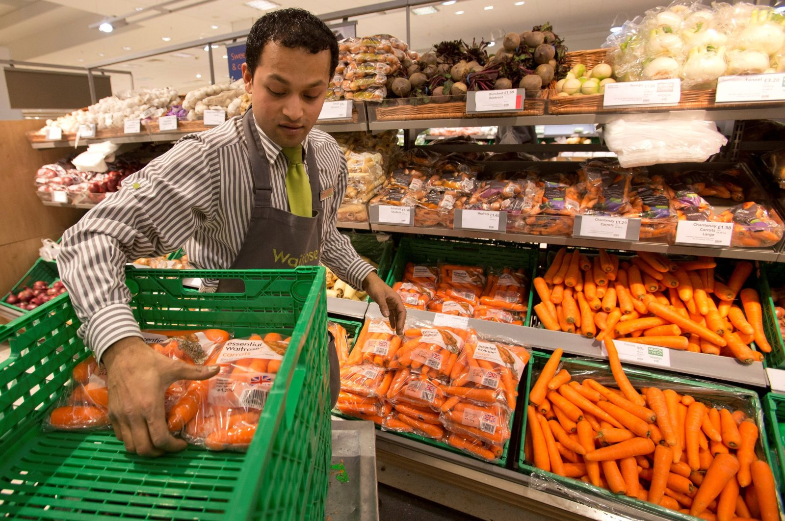 A supermarket worker stocks produce shelves in the Canary Wharf store of Waitrose, London, the U.K., Jan. 23, 2013. (REUTERS File Photo)