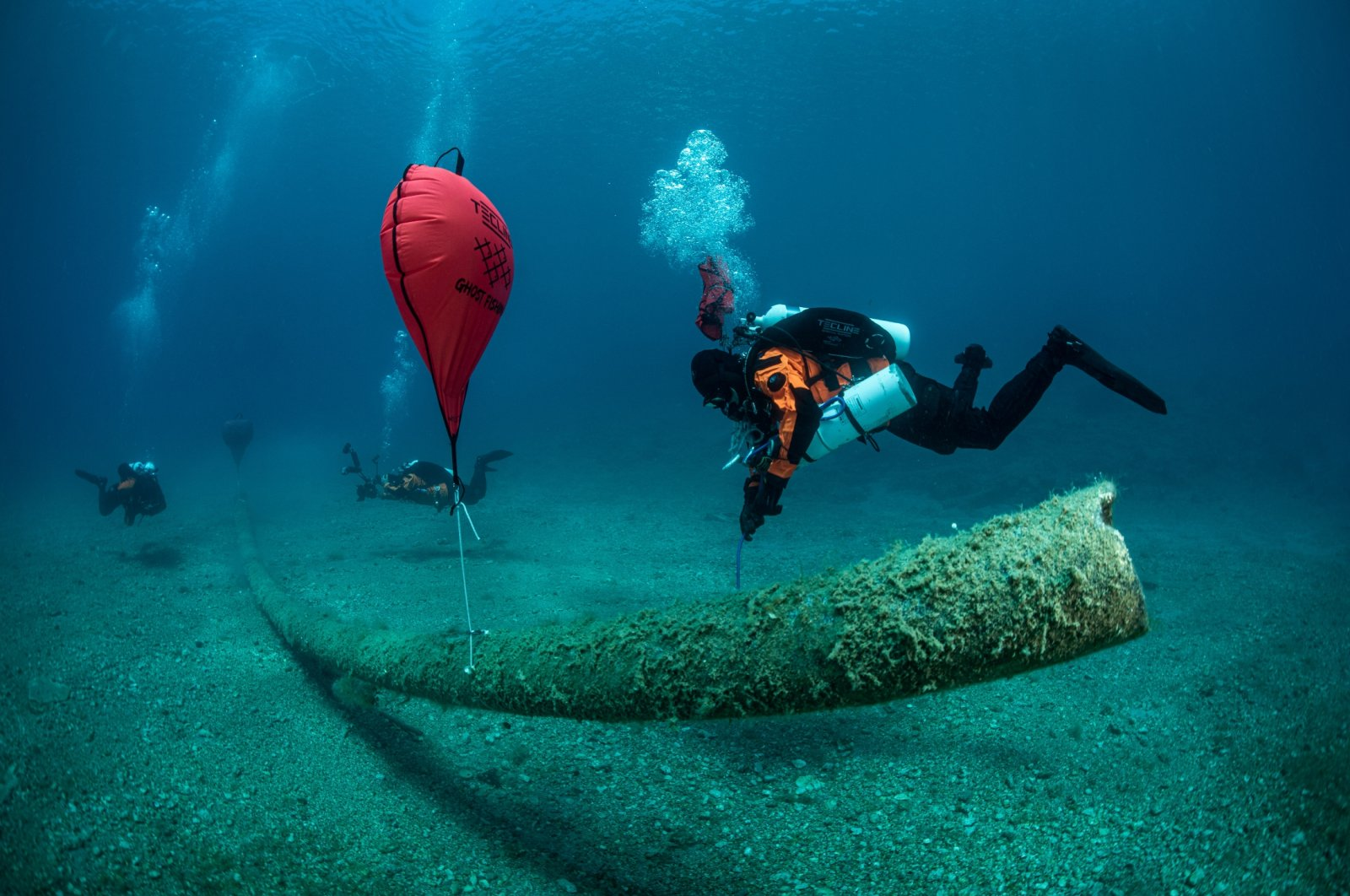 A diver inflates a lifting bag attached to the remains of a fish farm on the seabed, near the island of Ithaca, Greece, June 10, 2021. (Ghost Diving via Reuters)