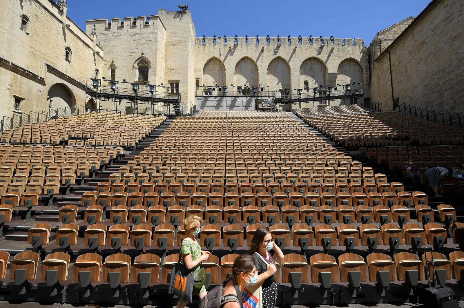 """People stand in the """"Cour d'honneur"""" of the Popes' Palace (Palais des papes) stage on the first day of this year's edition of the Avignon theatre festival in Avignon, France, July 5, 2021. (AFP Photo)"""