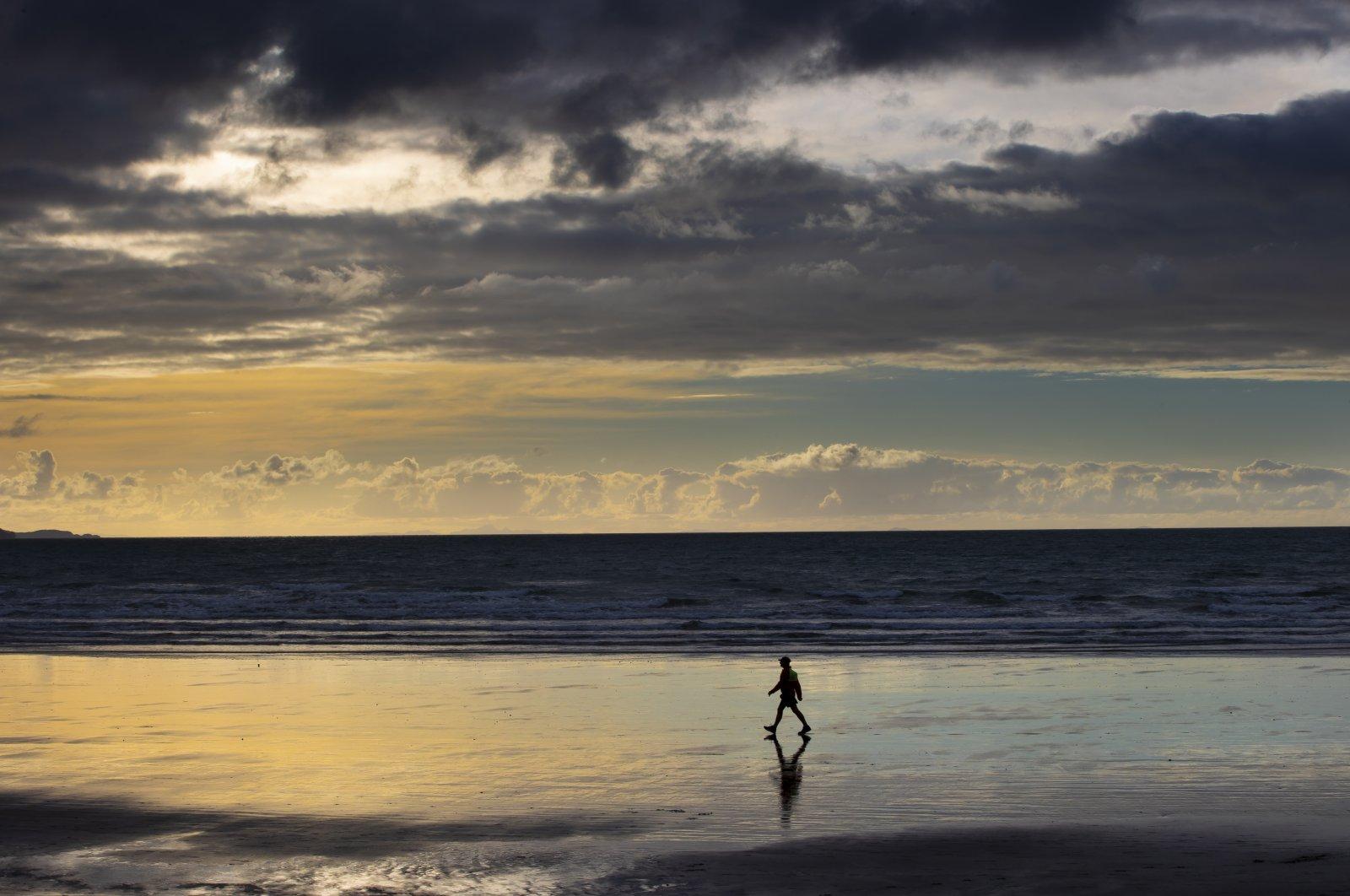 A person walks on Orewa Beach in Auckland, New Zealand, June 5, 2021. (AP Photo)